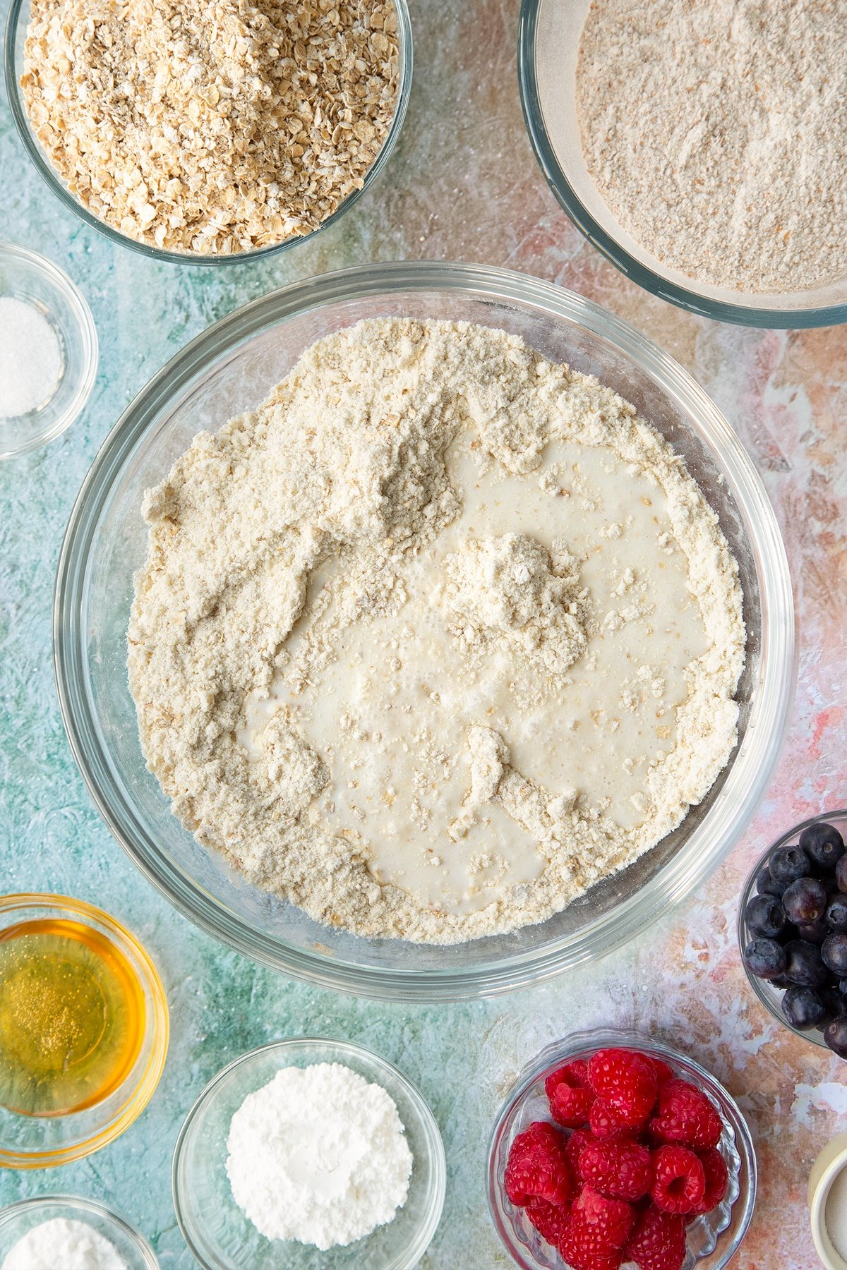 Butter rubbed into self-raising flour, bicarbonate of soda, sugar and oats in a glass mixing bowl with milk on top. Ingredients to make oatmeal scones surround the bowl.