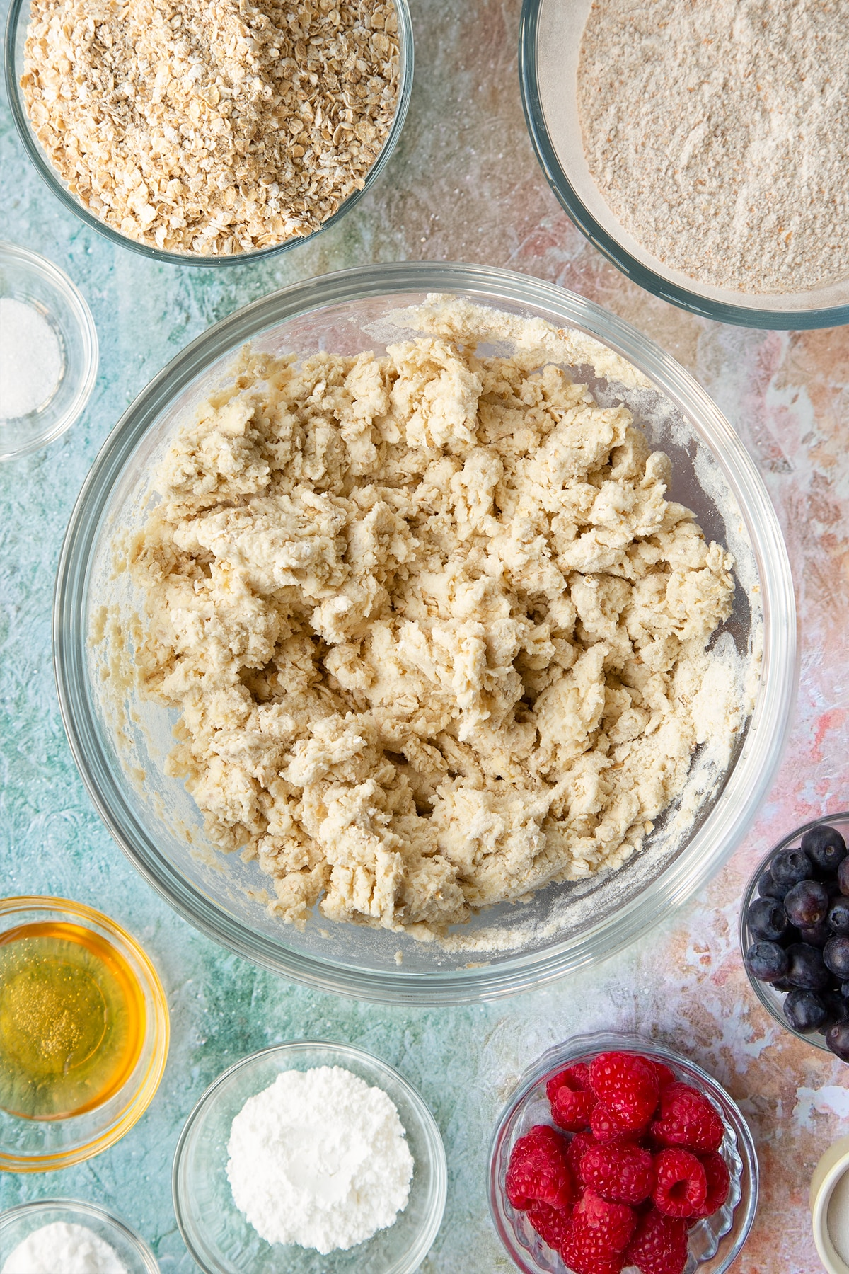 Oatmeal scone dough in a glass mixing bowl. Ingredients to make oatmeal scones surround the bowl.