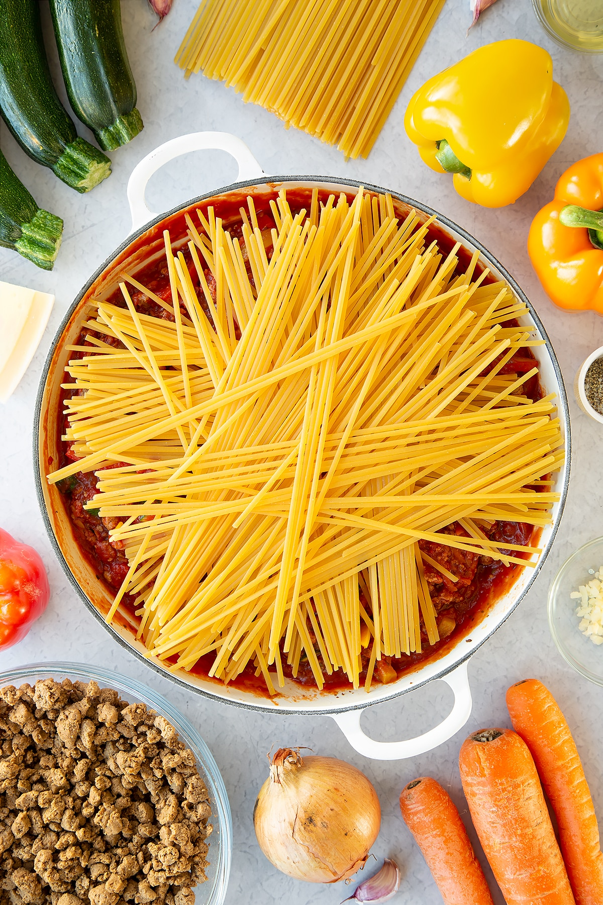 Veggie mince, garlic, onion, courgette, carrot, peppers and pasta sauce in a large pan with dried linguine on top. Ingredients to make one pot vegan bolognese surround the pan.