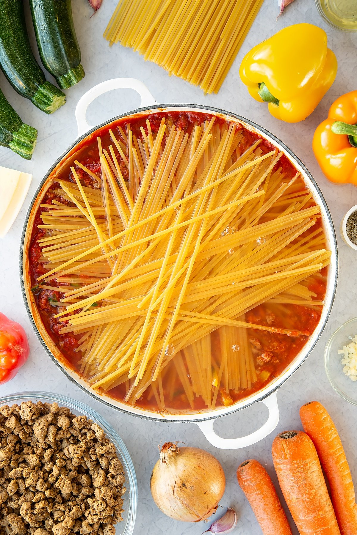 Veggie mince, garlic, onion, courgette, carrot, peppers and pasta sauce in a large pan with dried linguine on top, covered with boiling water. Ingredients to make one pot vegan bolognese surround the pan.
