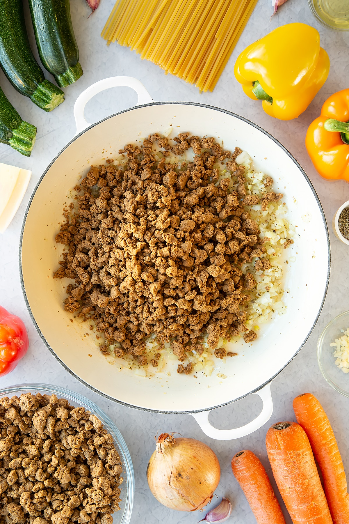 Seasoned garlic and onion sweated in a large pan with meat-free mince on top. Ingredients to make one pot vegan bolognese surround the pan.