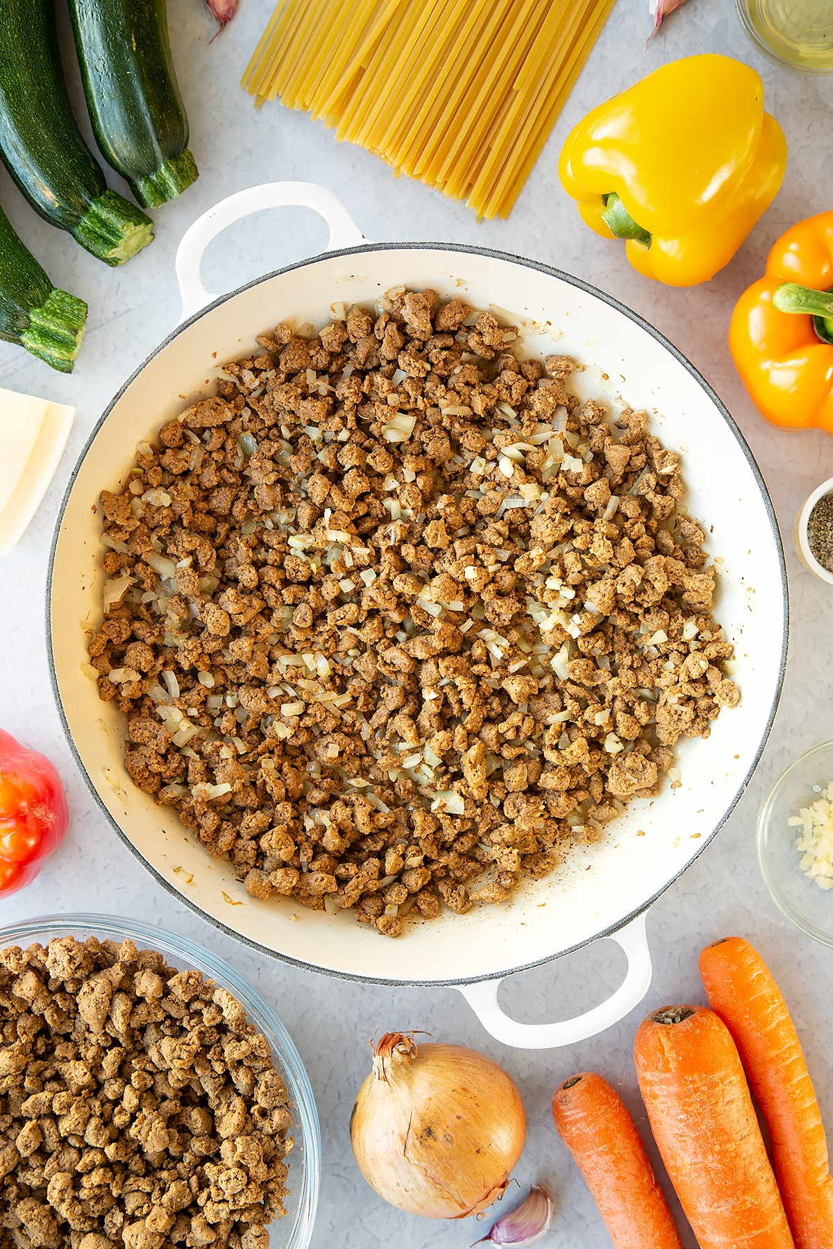 Veggie mince, garlic and onion sweated in a large pan. Ingredients to make one pot vegan bolognese surround the pan.