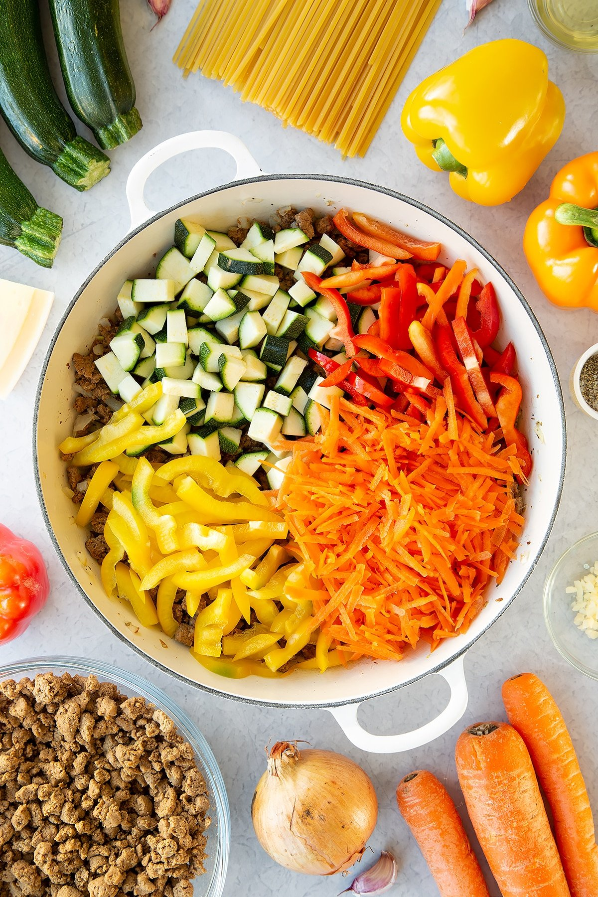 Veggie mince, garlic and onion sweated in a large pan with courgette, carrot and peppers on top. Ingredients to make one pot vegan bolognese surround the pan.