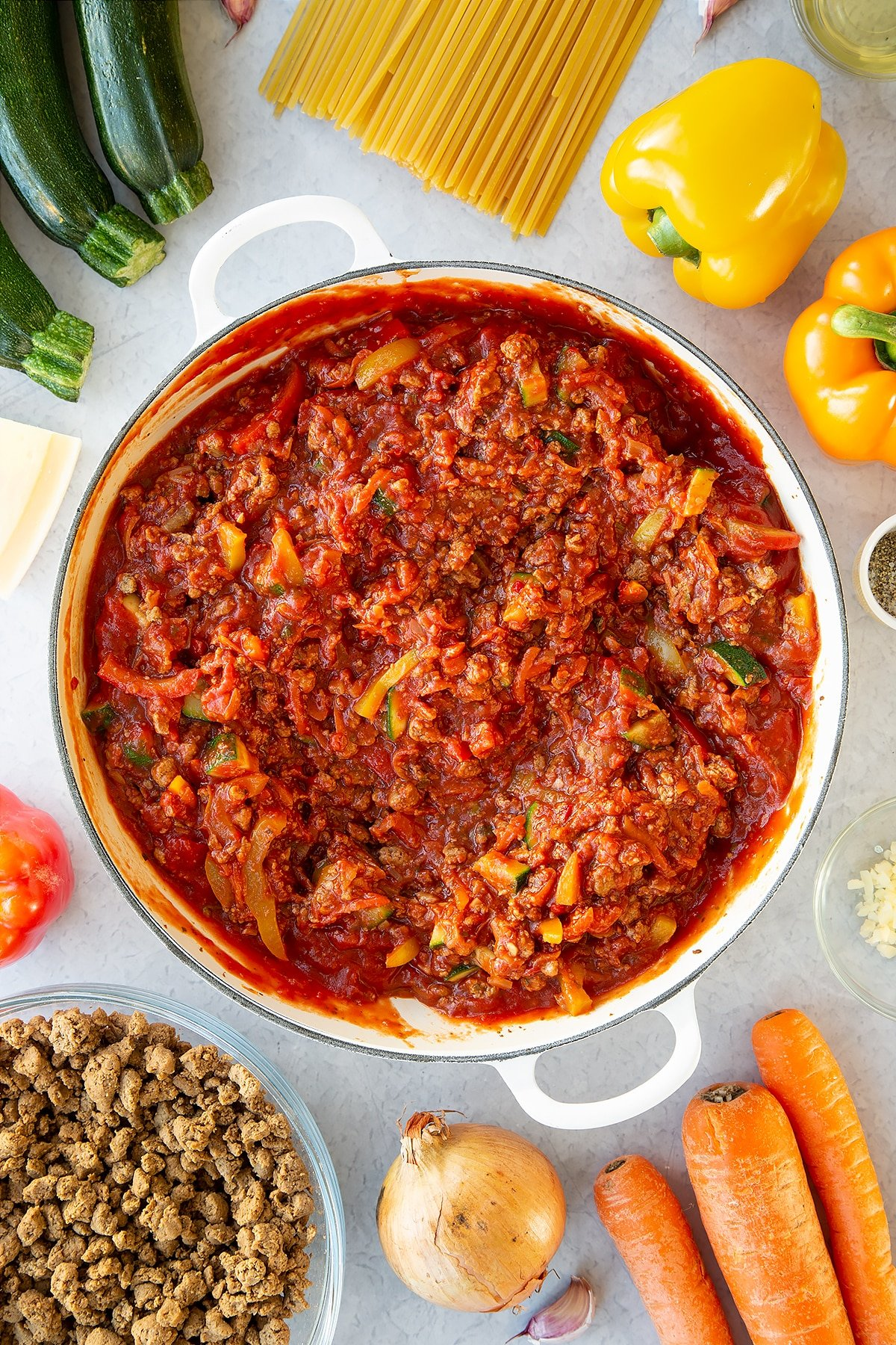 Veggie mince, garlic, onion, courgette, carrot, peppers and pasta sauce in a large pan. Ingredients to make one pot vegan bolognese surround the pan.