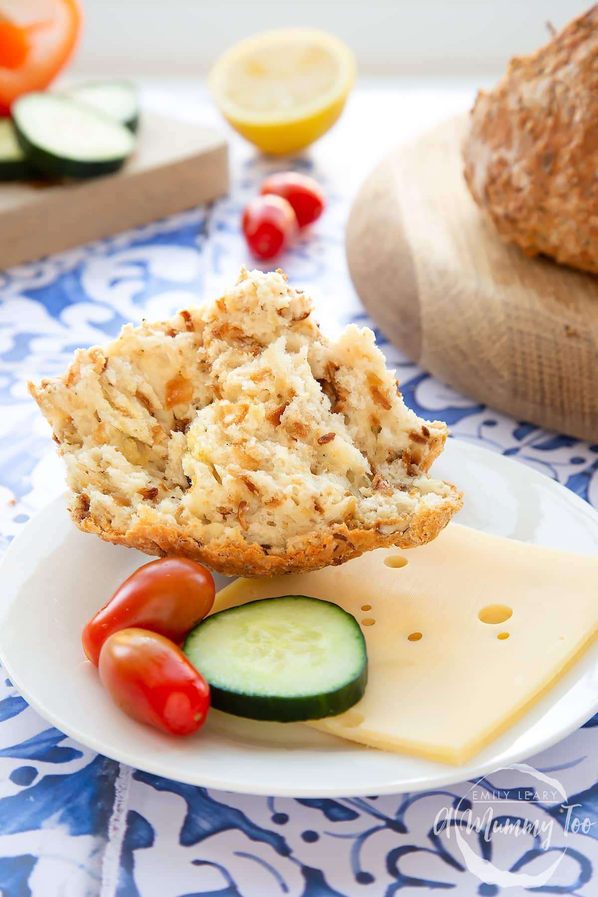 A piece of onion soda bread on a small white plate with sliced cheese, cucumber and cherry tomatoes.