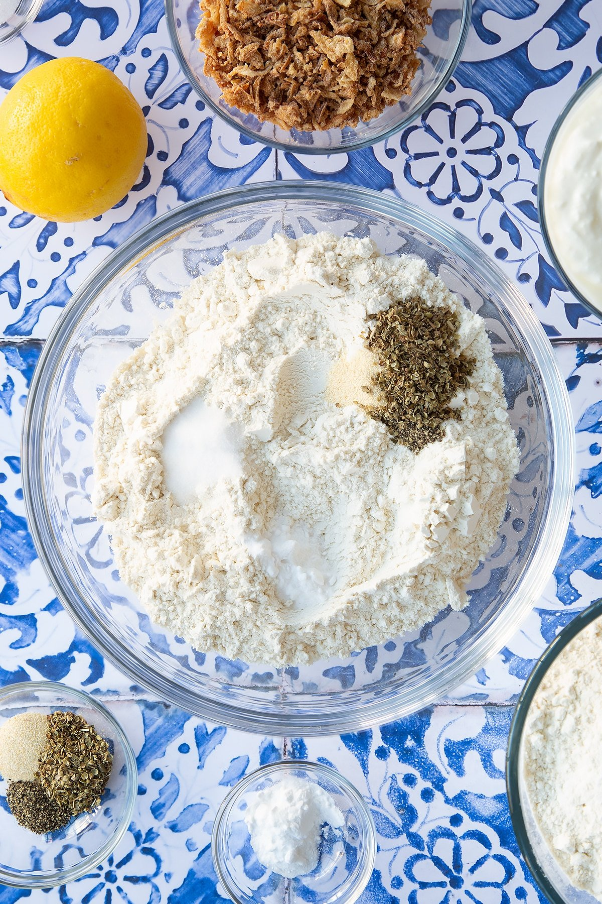 Flour, salt, bicarbonate of soda, garlic granules, oregano, salt and pepper in a mixing bowl. Ingredients to make onion soda bread surround the bowl.