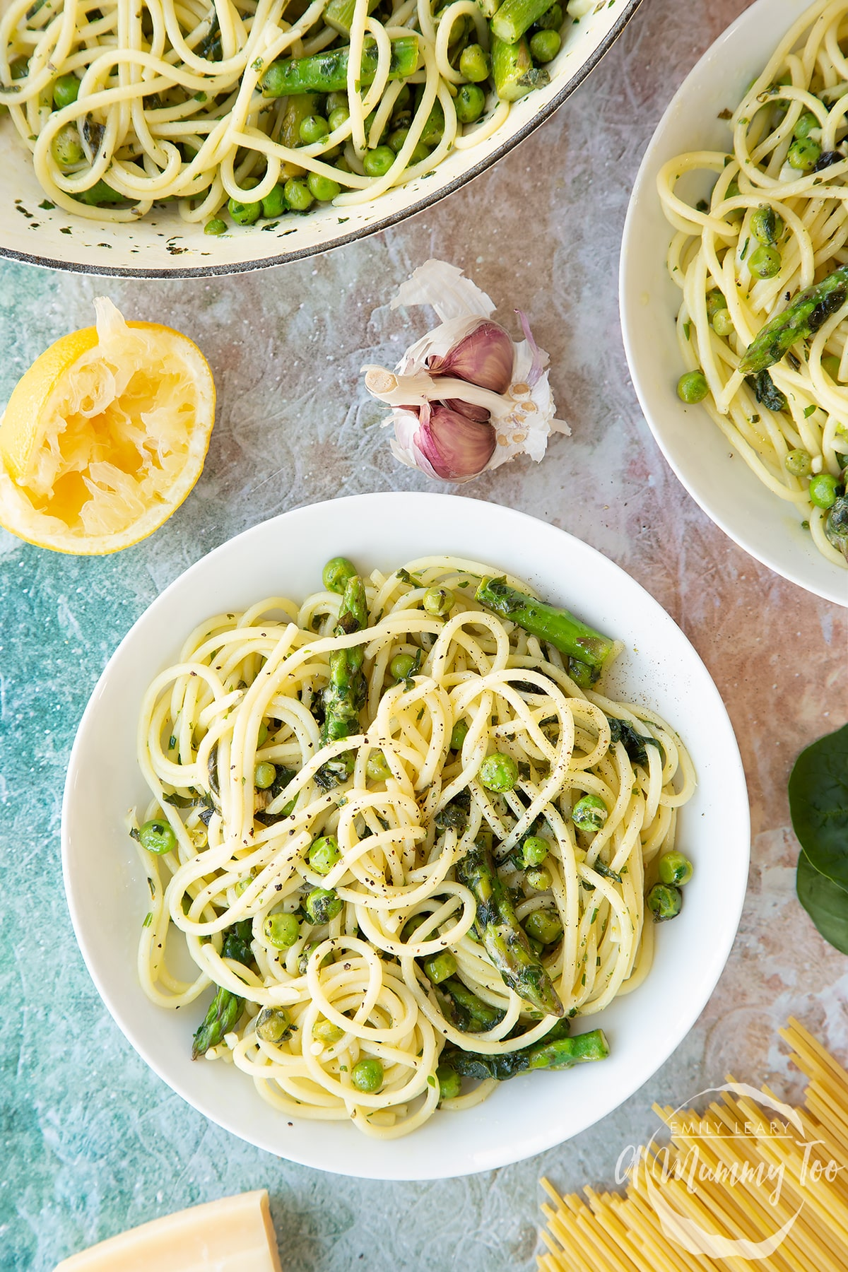 Summer spaghetti with spinach, basil, asparagus and peas, served in white bowls. Shown from above.