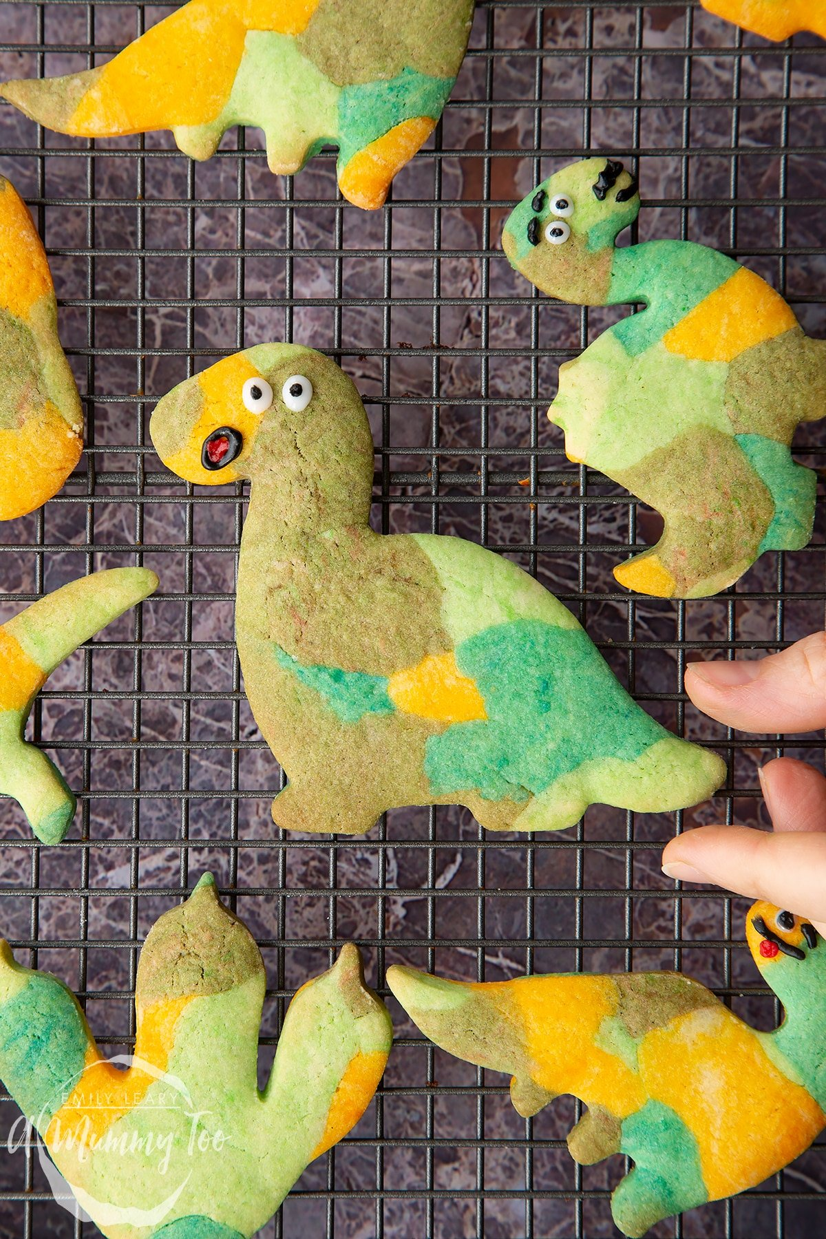 Overhead shot of baked multicoloured dinosaur cookie dough shapes with smiley faces on a wire rack