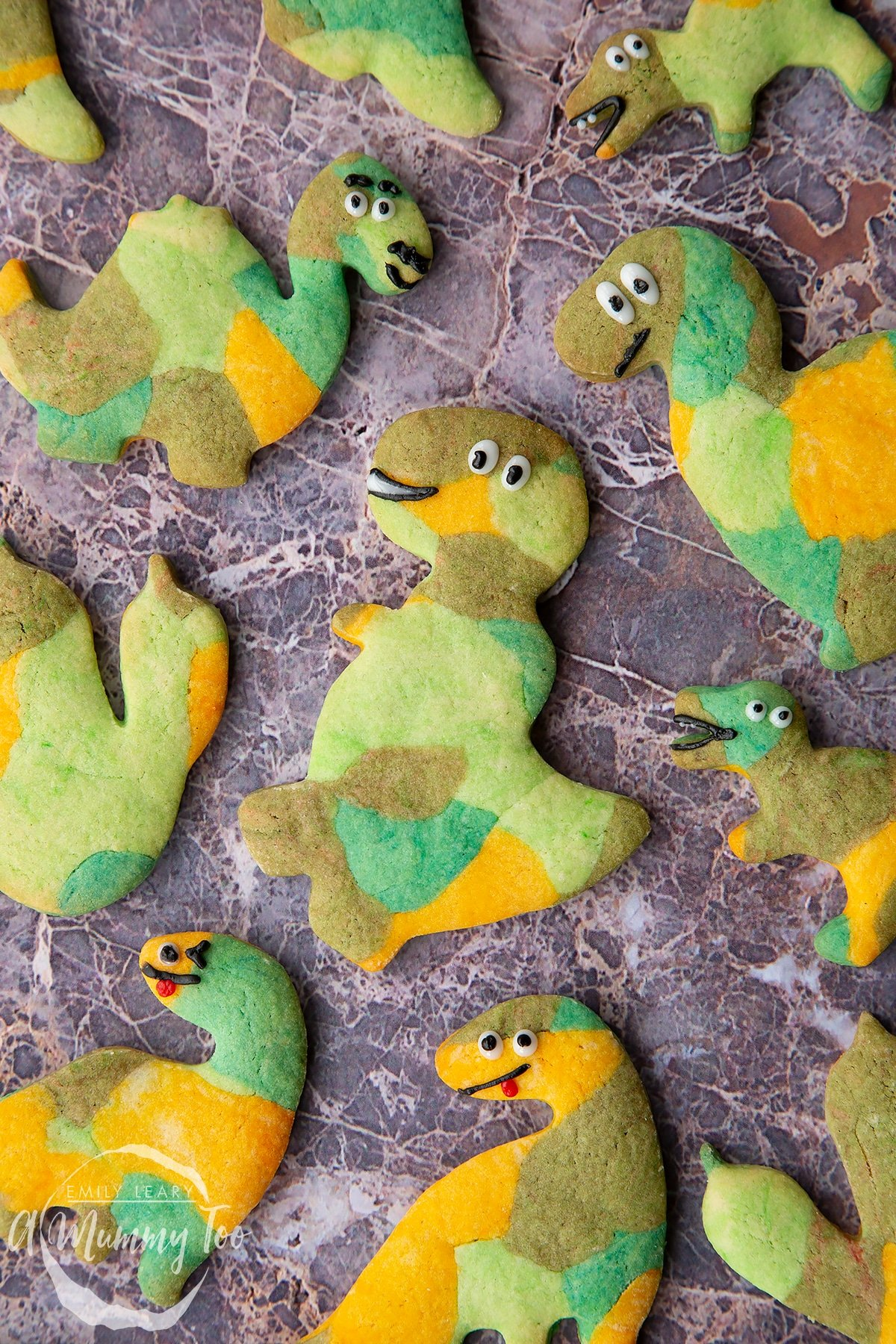 Overhead shot of green dinosaur cookies with the A Mummy Too logo in the corner