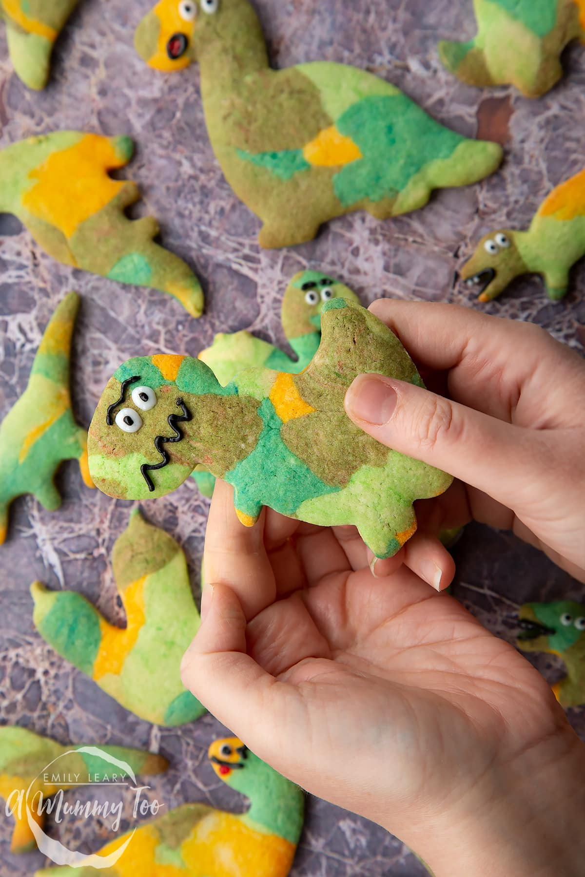 Overhead shot of a hand holding a green dinosaur cookie with the A Mummy Too logo in the corner