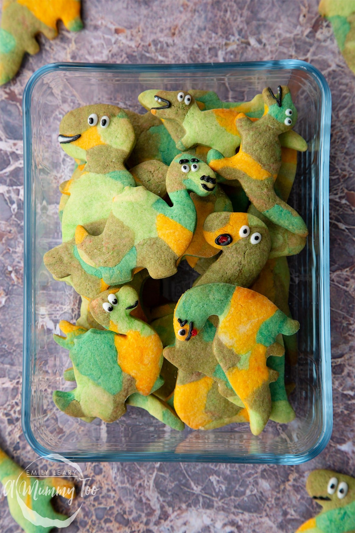 Overhead shot of dinosaur cookies stacked in a clear glass casserole dish with A Mummy Too logo in the corner