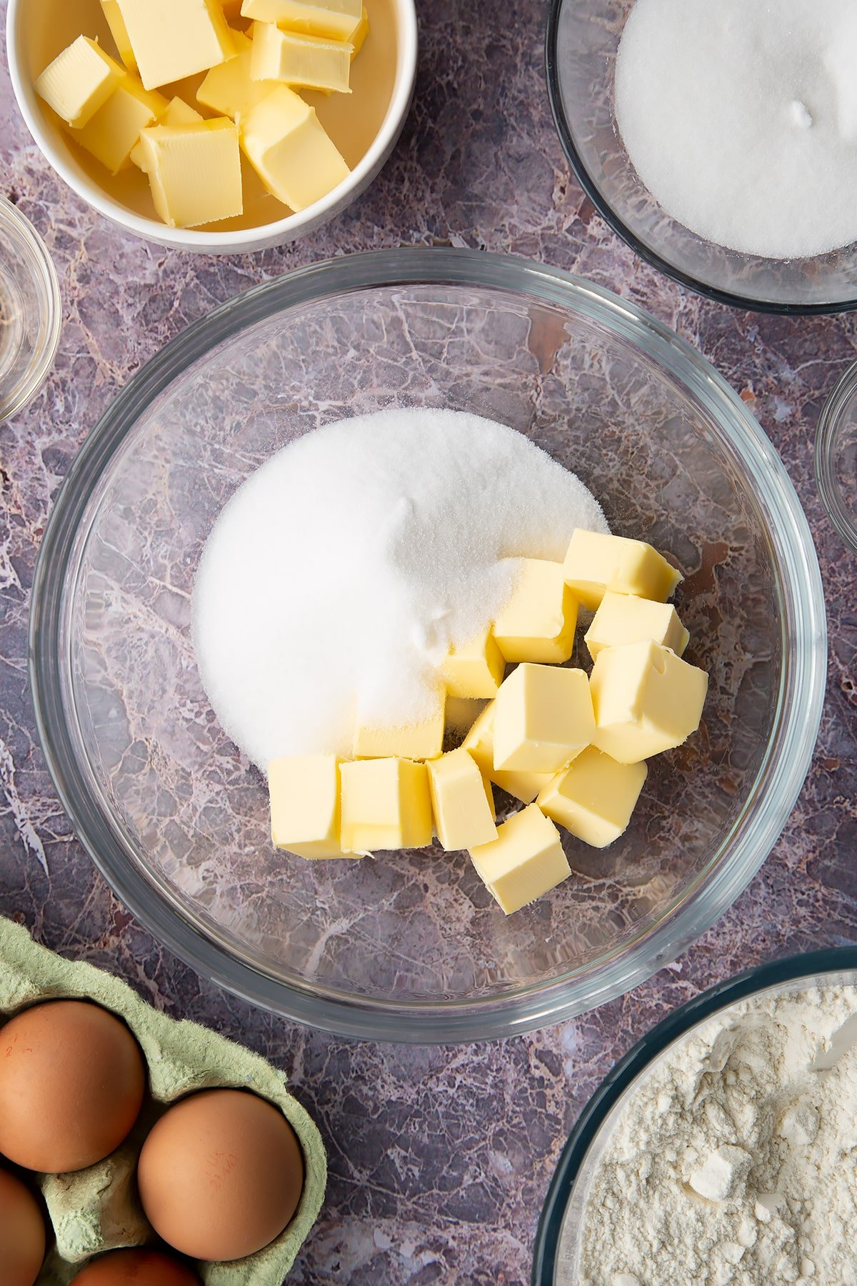 Overhead shot of butter cubes and sugar in a large clear bowl