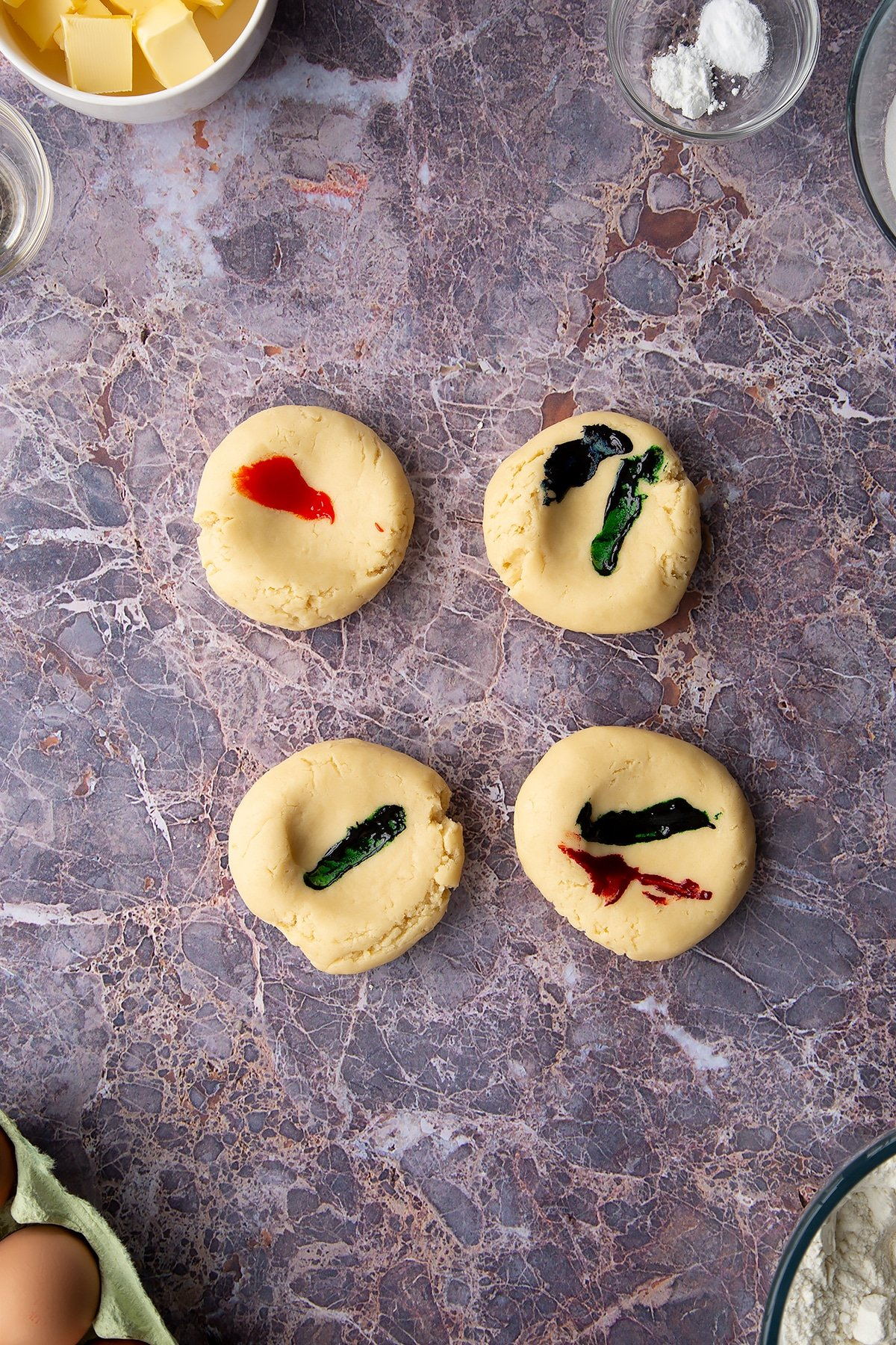 Overhead shot of 4 round pieces of cookie dough with food colouring painted on top