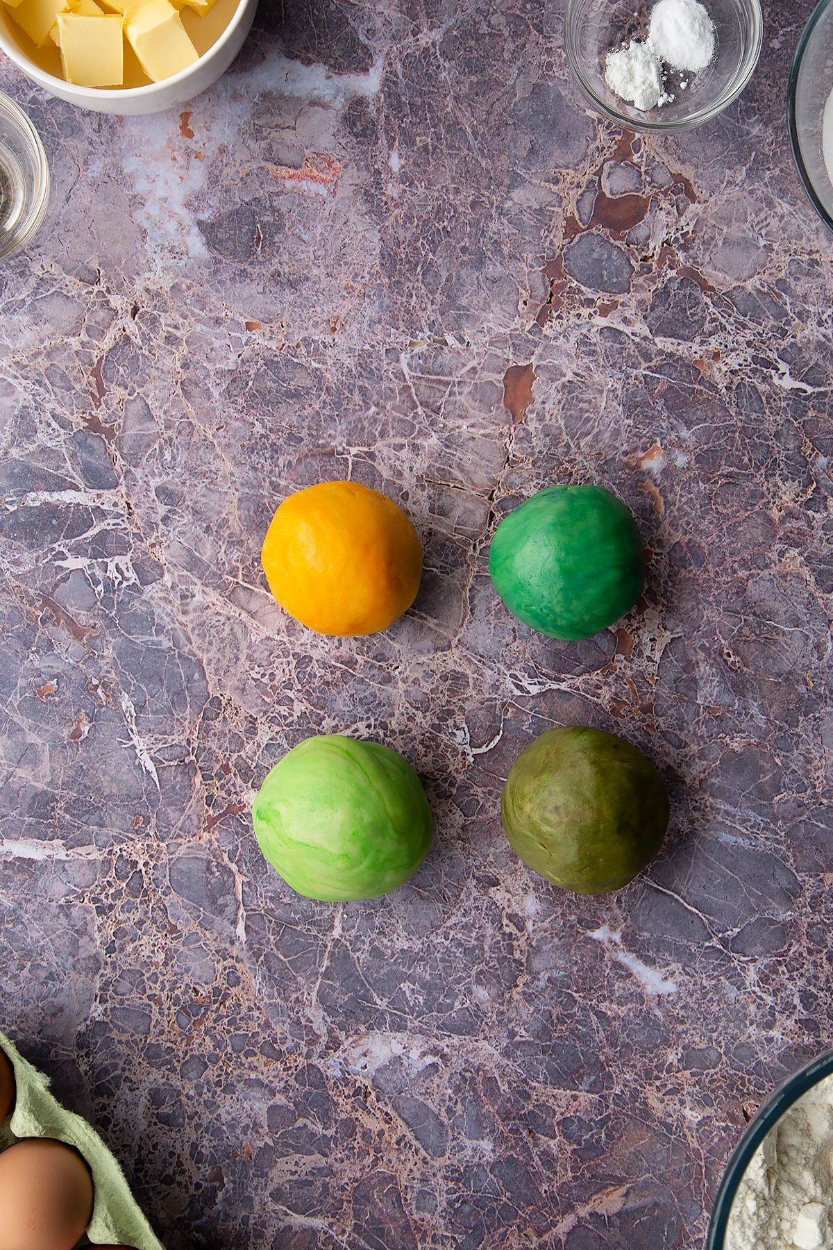 Overhead shot of 4 coloured cookie dough balls