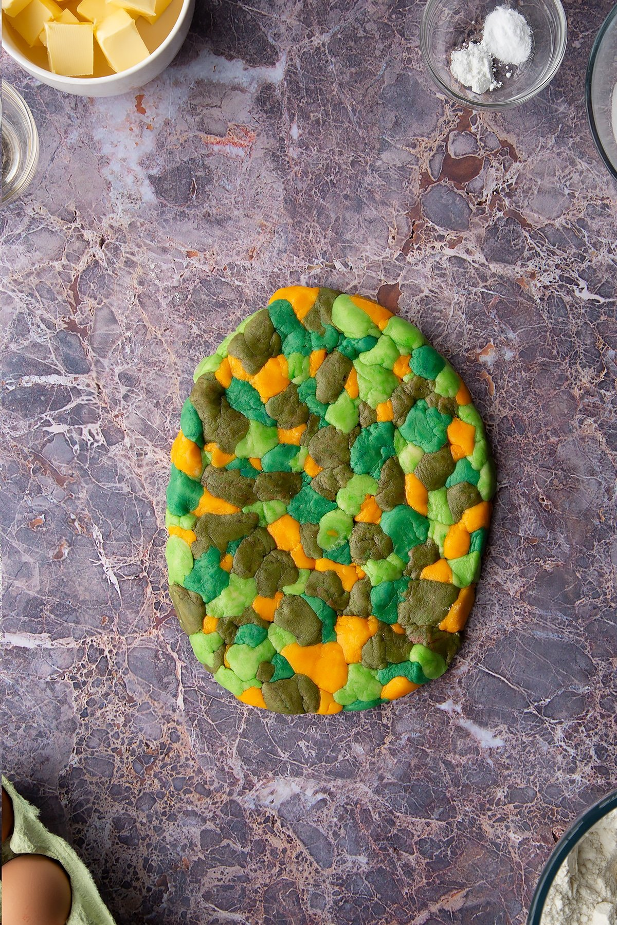 Overhead shot of small chunks of coloured cookie dough pieces laid out together on a surface combines together