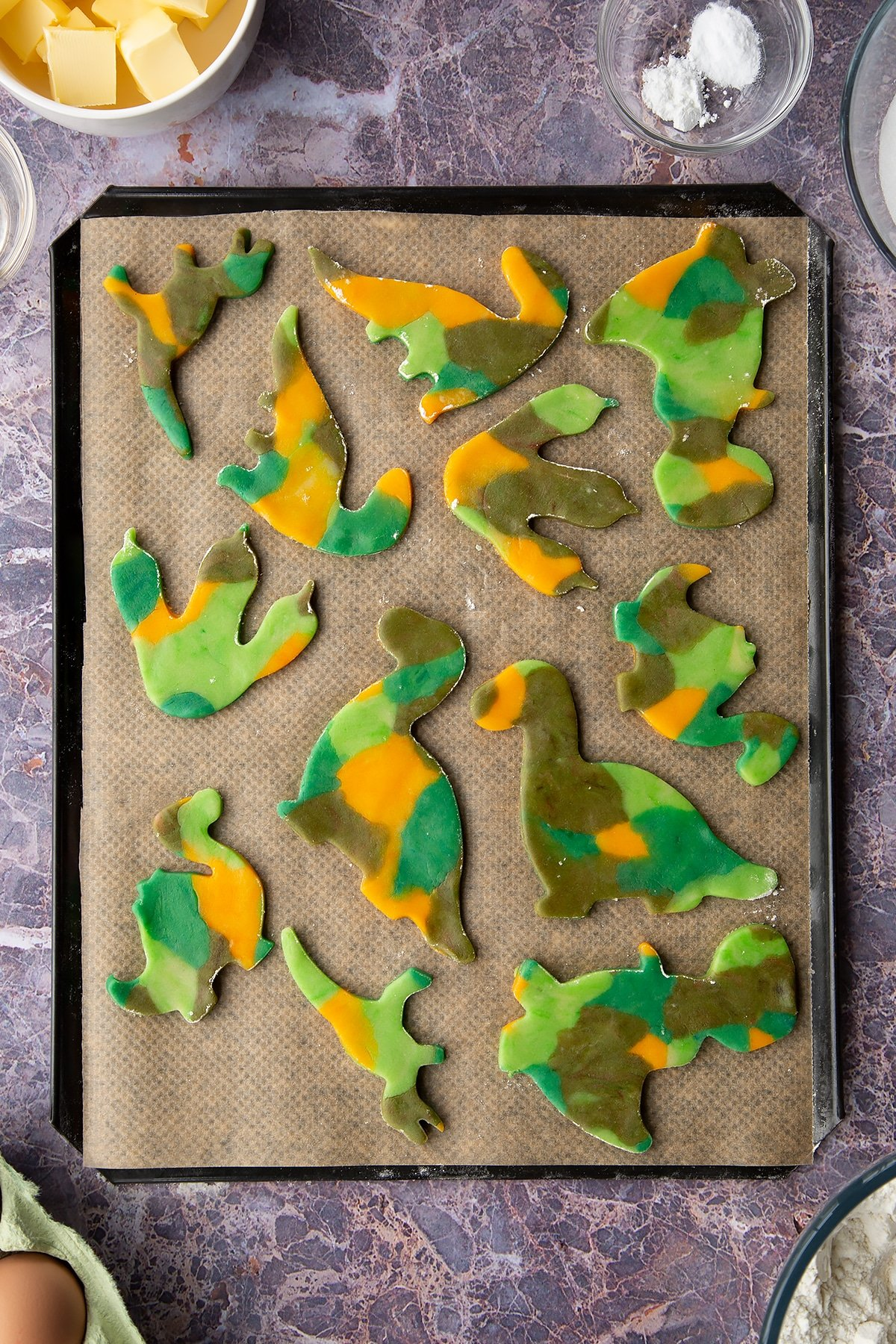 Overhead shot of multicoloured dinosaur cookie dough shapes on a lined baking tray