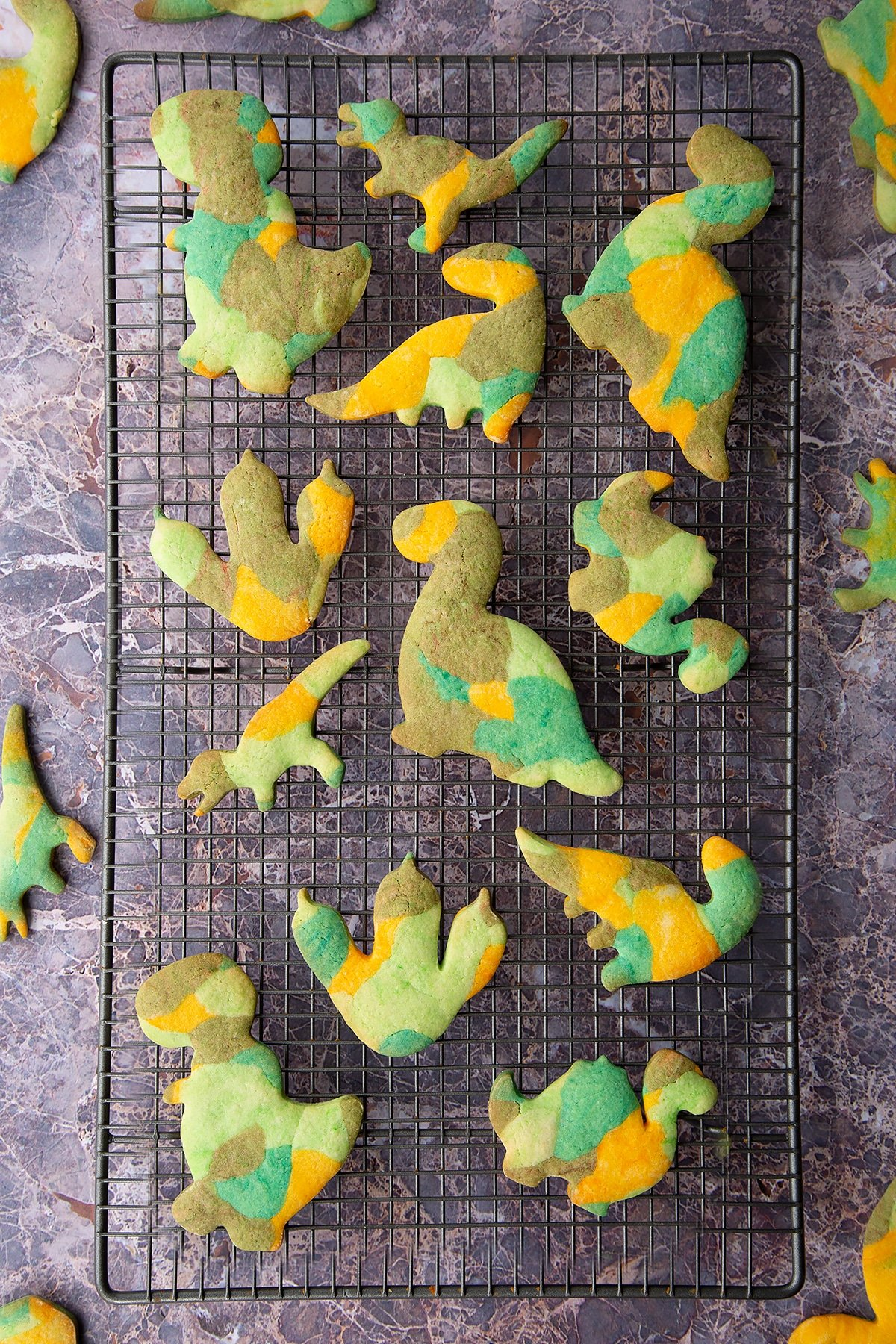 Overhead shot of baked multicoloured dinosaur cookie dough shapes on a metal rack