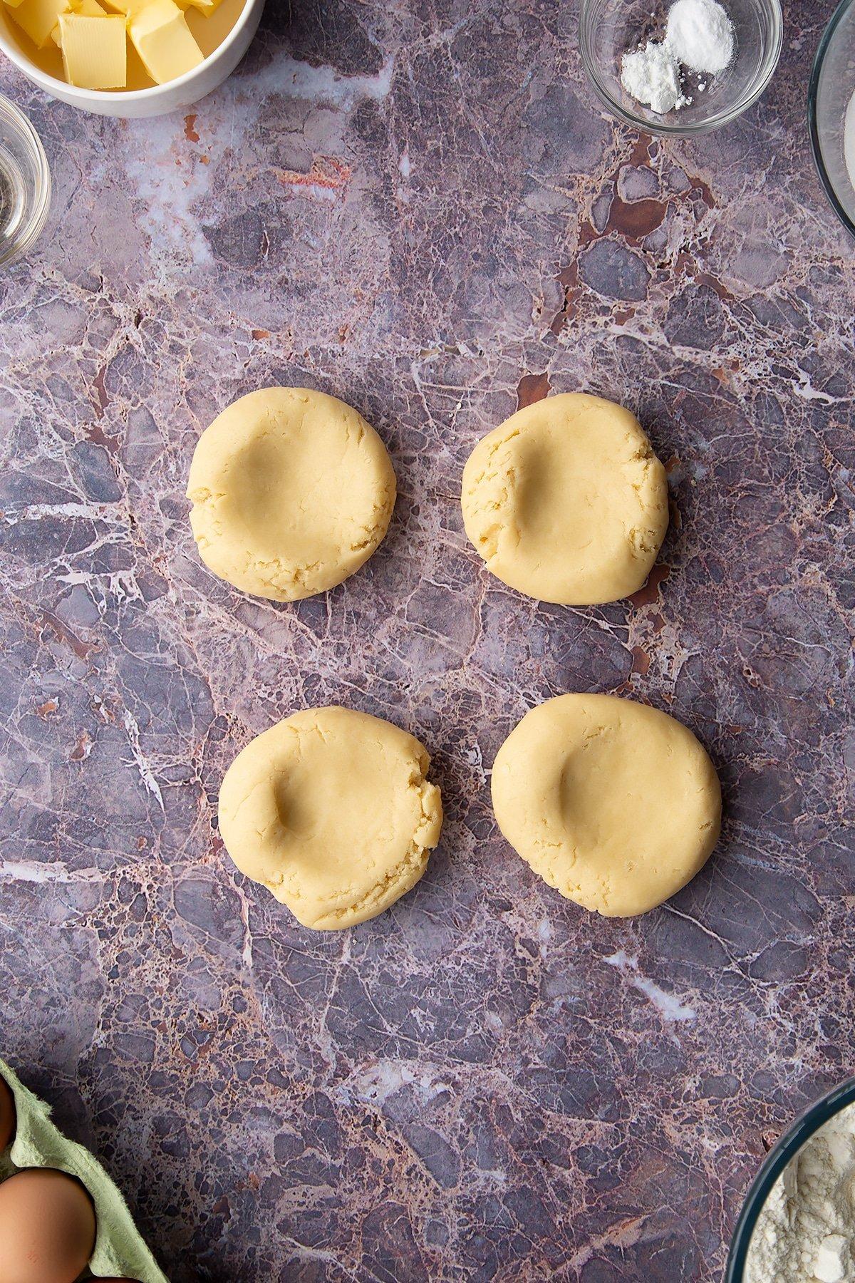 Overhead shot of cookie dough into four circular balls