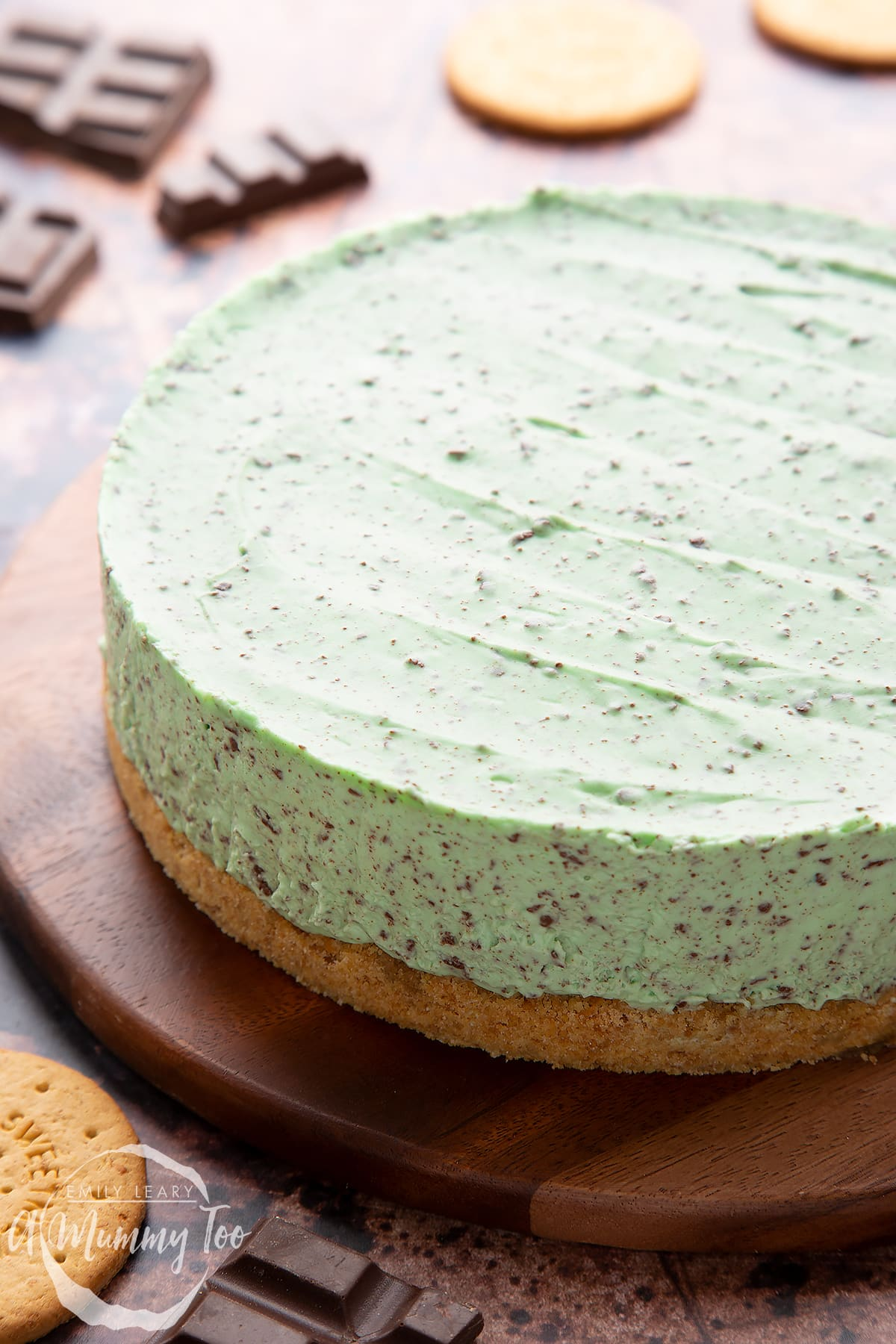 No bake mint cheesecake with a biscuit base on a wooden board.
