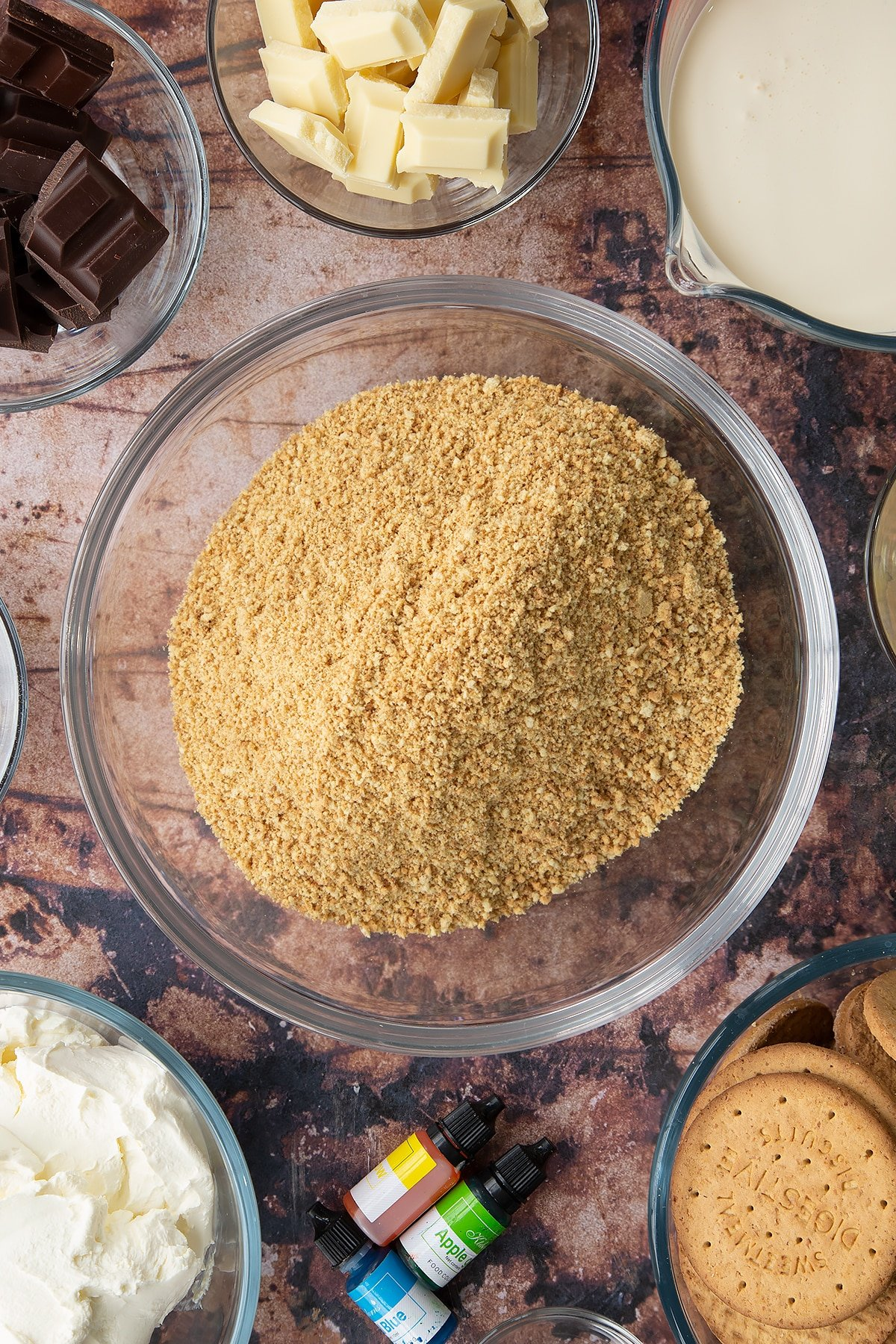 Crushed biscuits in a glass bowl. Ingredients to make no bake mint cheesecake surround the bowl.