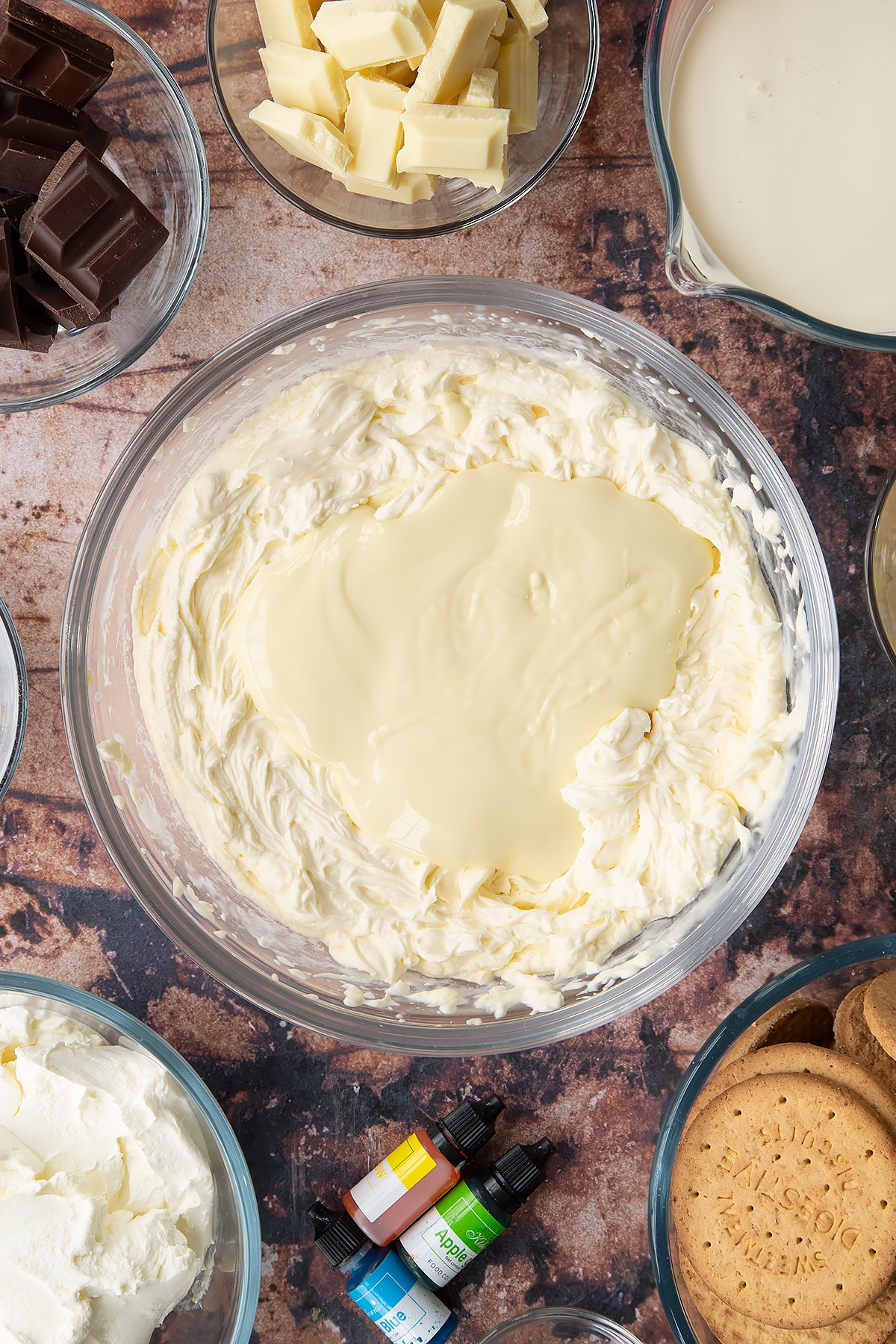 Double cream, cream cheese, peppermint extract and sugar, whisked together in a glass bowl with melted white chocolate on top. Ingredients to make no bake mint cheesecake surround the bowl.