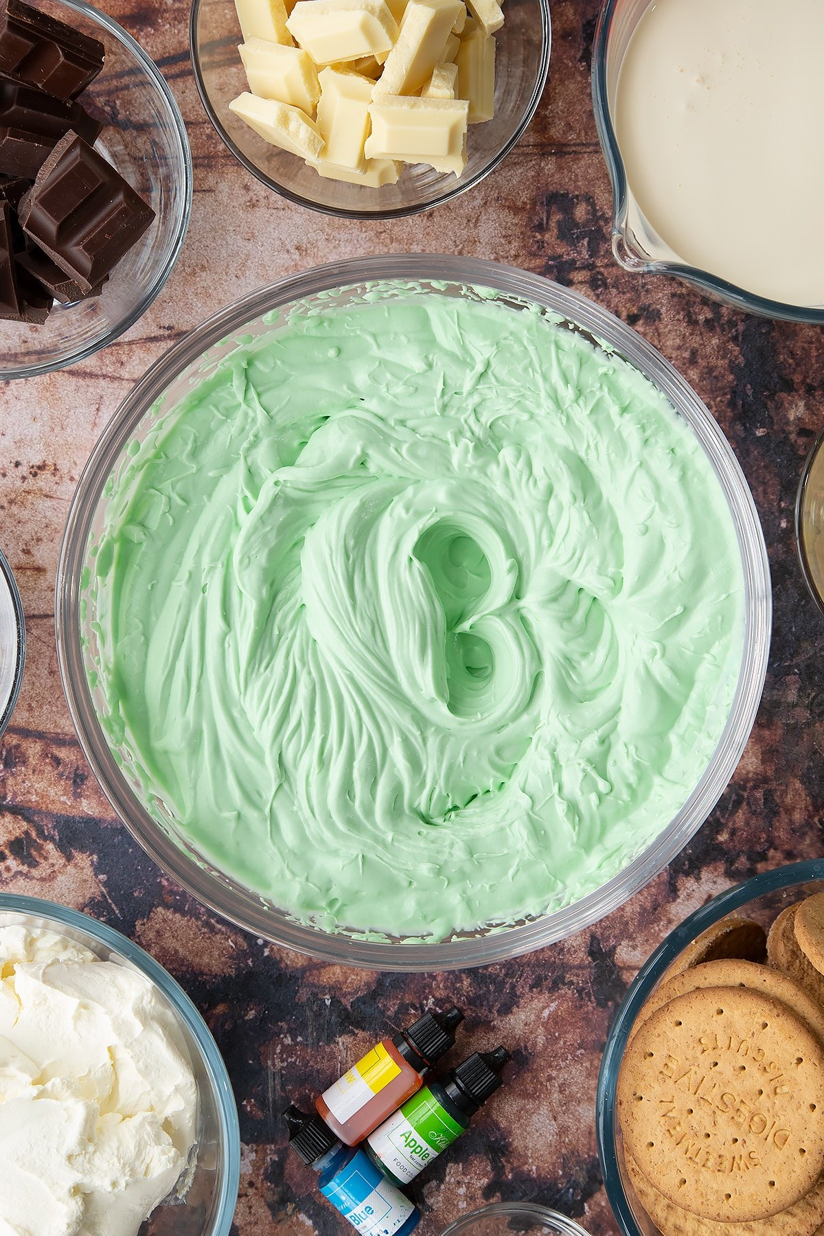 Peppermint green cheesecake filling in a glass bowl. Ingredients to make no bake mint cheesecake surround the bowl.