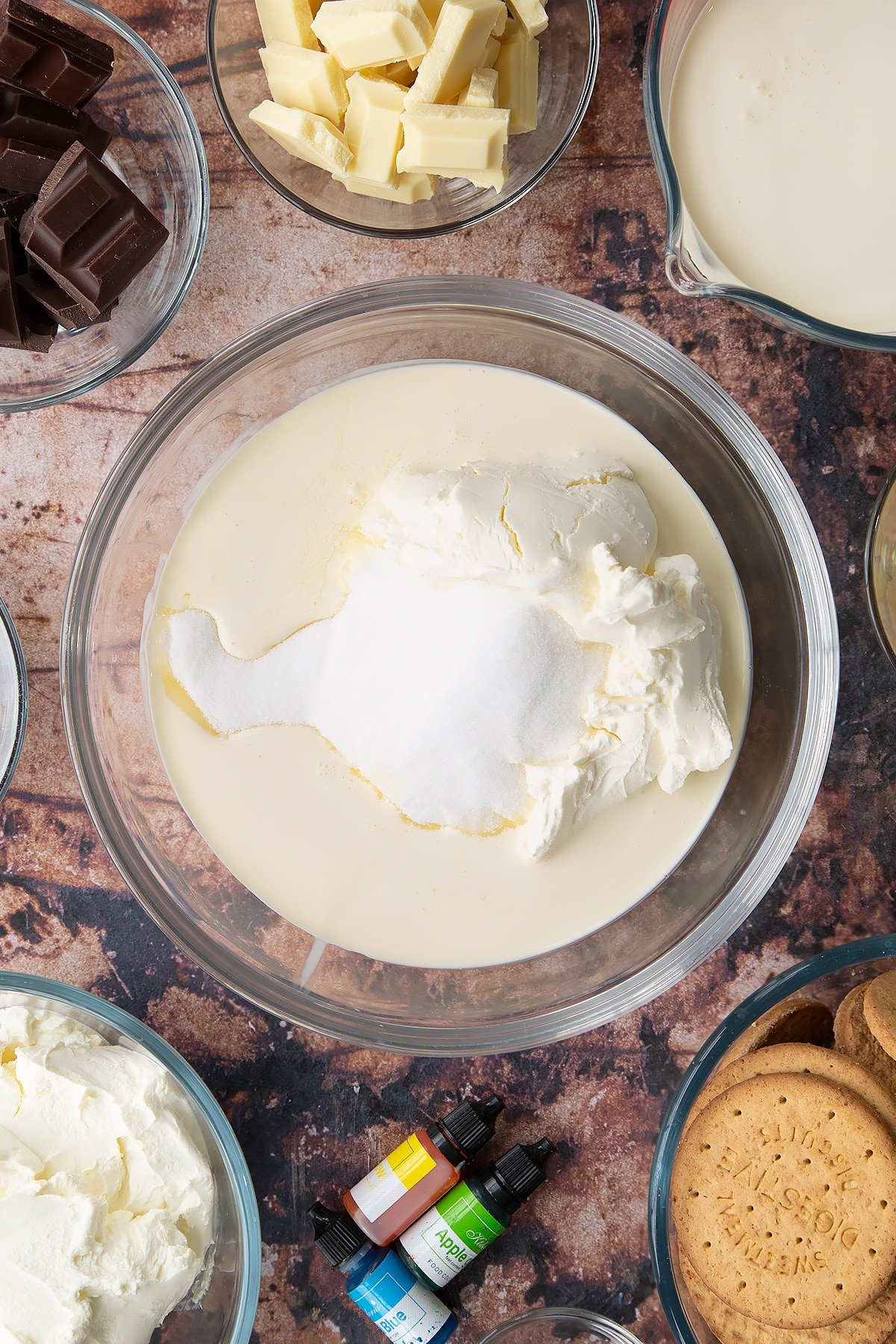Double cream, cream cheese, peppermint extract and sugar in a glass bowl. Ingredients to make no bake mint cheesecake surround the bowl.