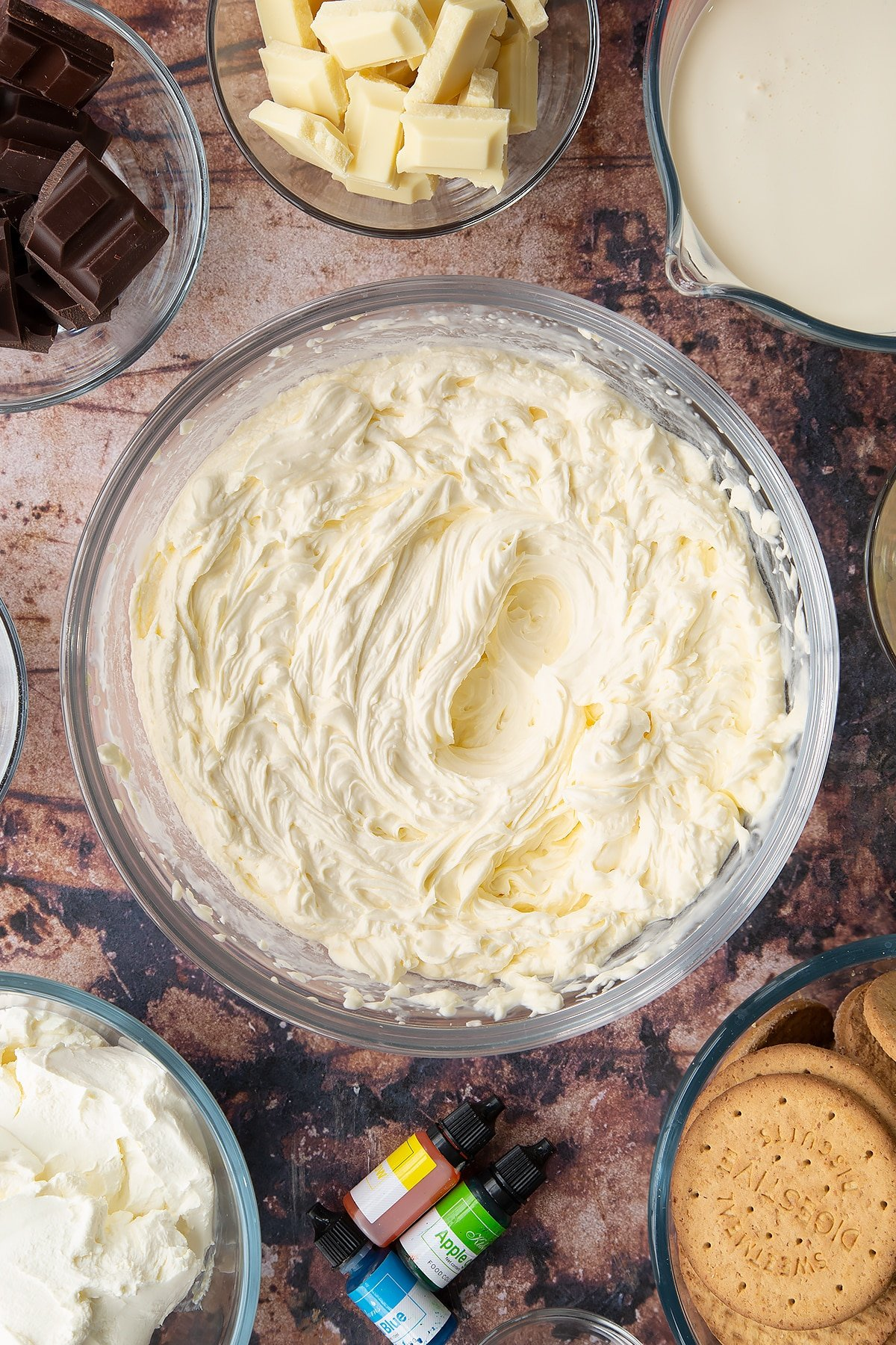 Double cream, cream cheese, peppermint extract and sugar, whisked together in a glass bowl. Ingredients to make no bake mint cheesecake surround the bowl.