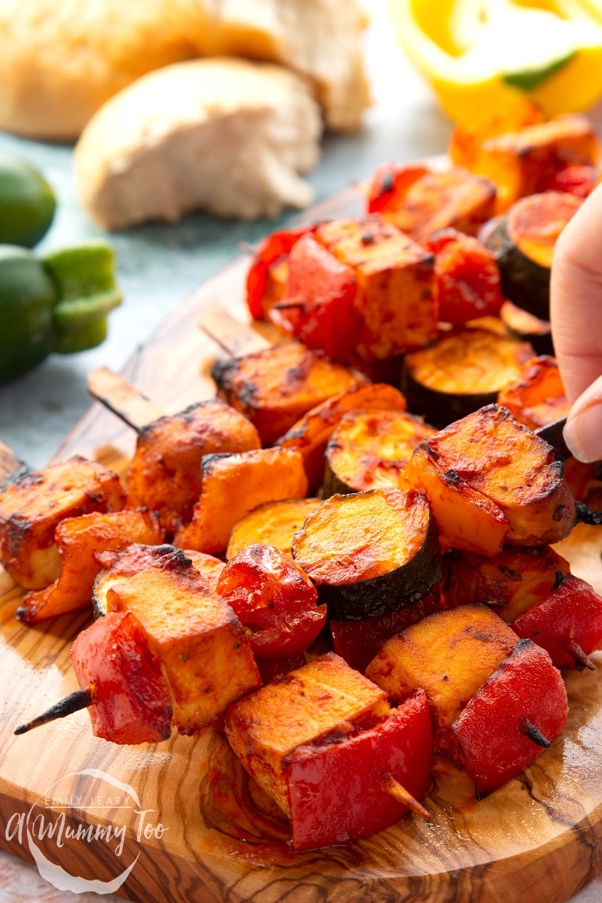 Tofu skewers piled on a wooden board. A hand reaches for one