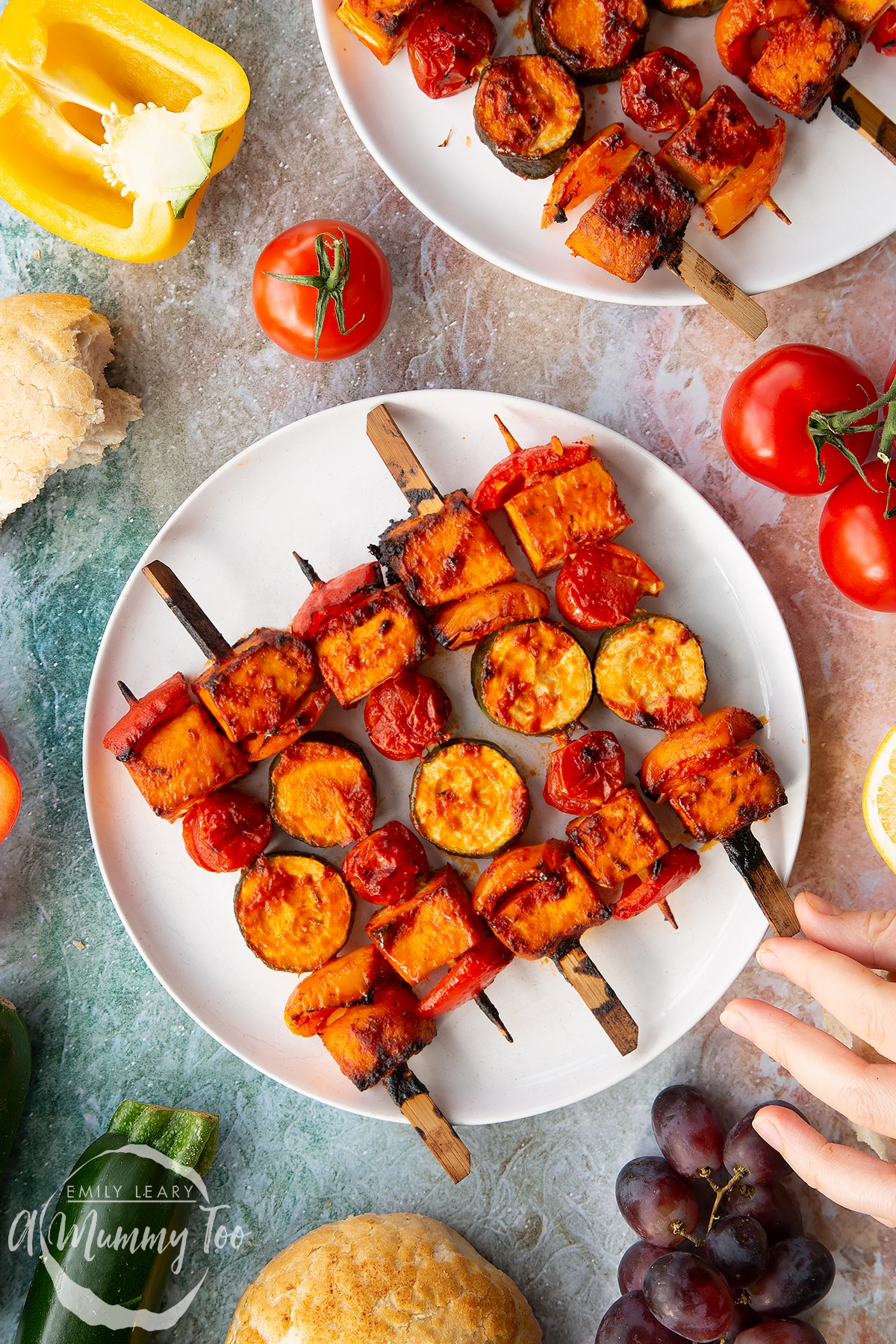 Tofu skewers arranged on a white plate. A hand reaches for one.