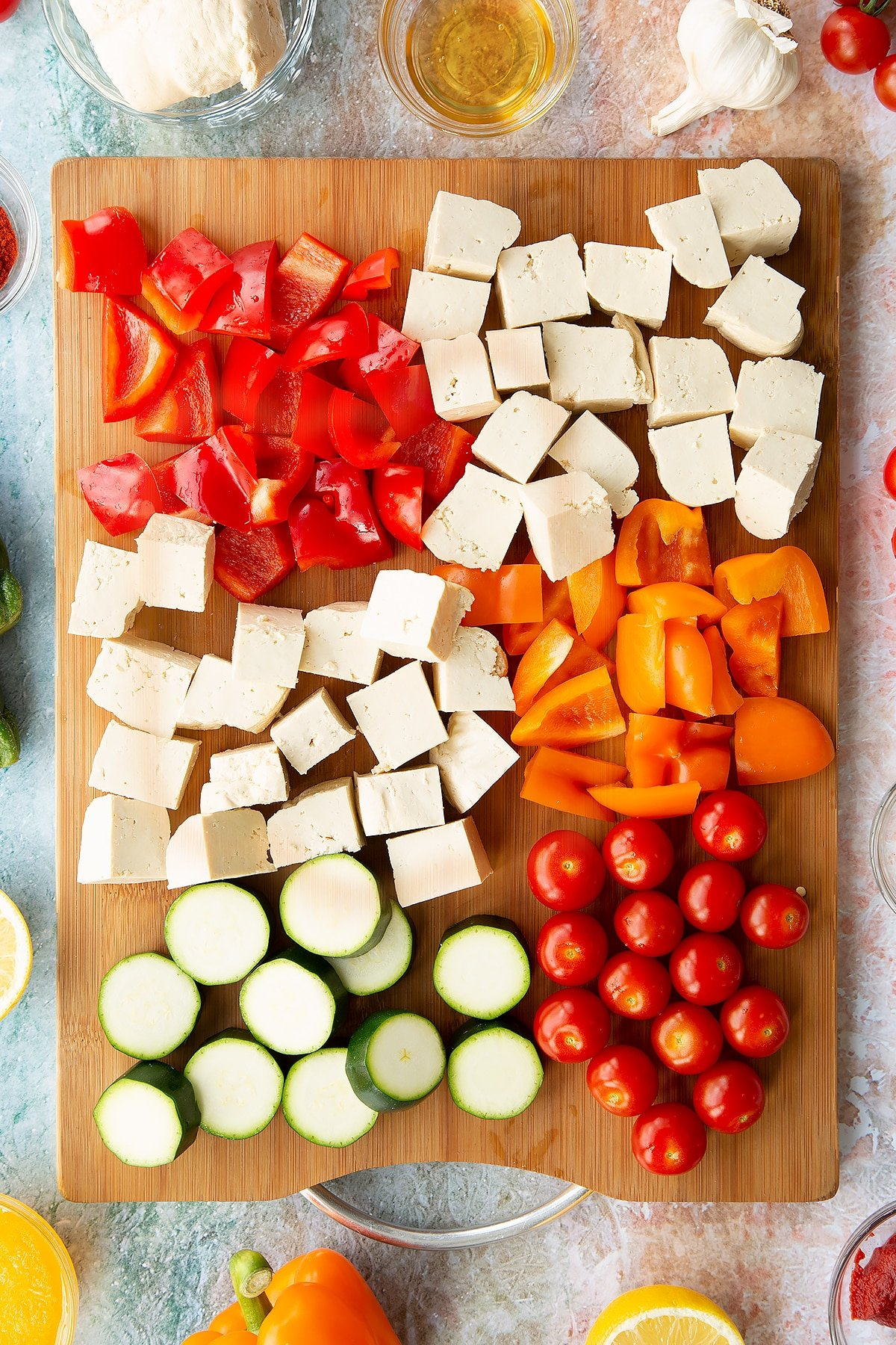 All the ingredients for the tofu skewers on a board: whole cherry tomatoes, thickly sliced courgette, chopped red and orange peppers, cubed tofu.
