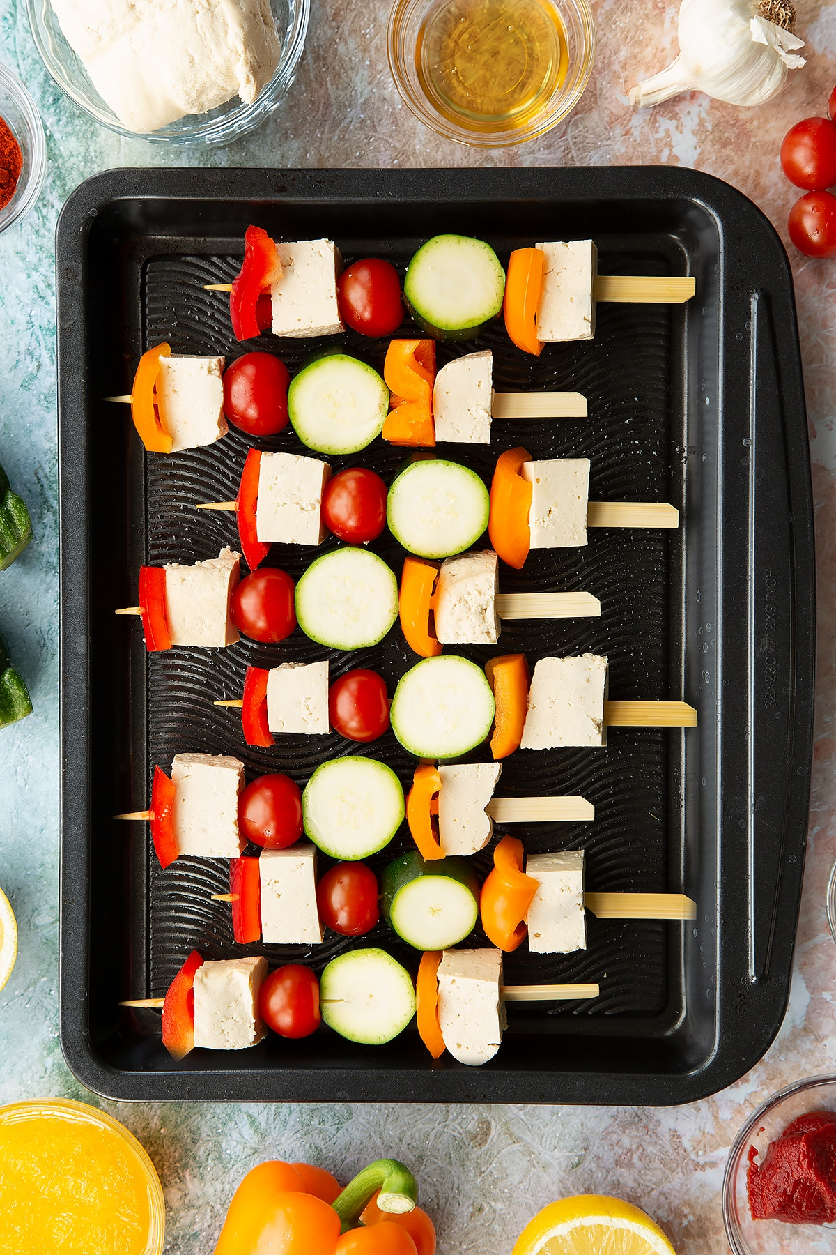 Raw tofu skewers lined up on a baking tray.