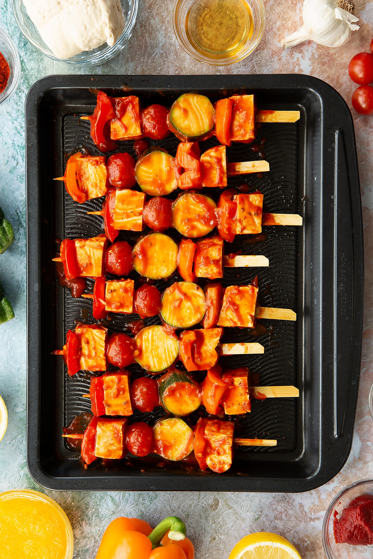 Tofu skewers lined up, brushed with marinade and ready to cook on a baking tray.