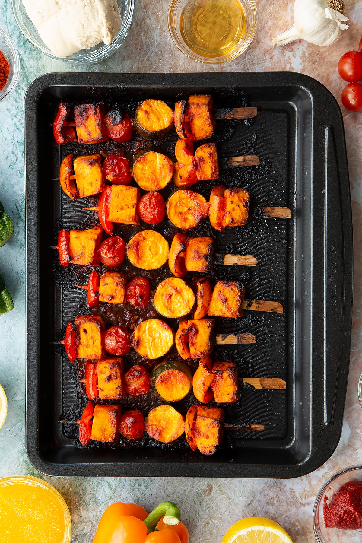 Cooked tofu skewers lined up on a baking tray.