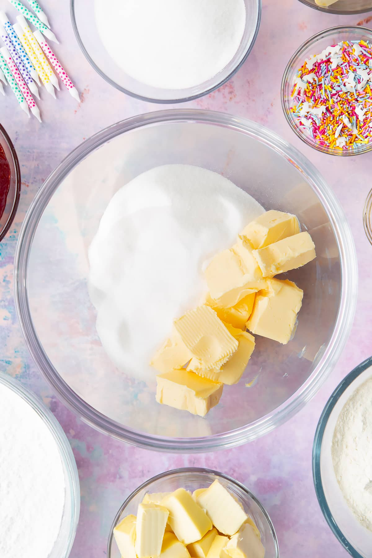Vegan butter and caster sugar in a glass mixing bowl. Ingredients to make vegan birthday cake surround the bowl.