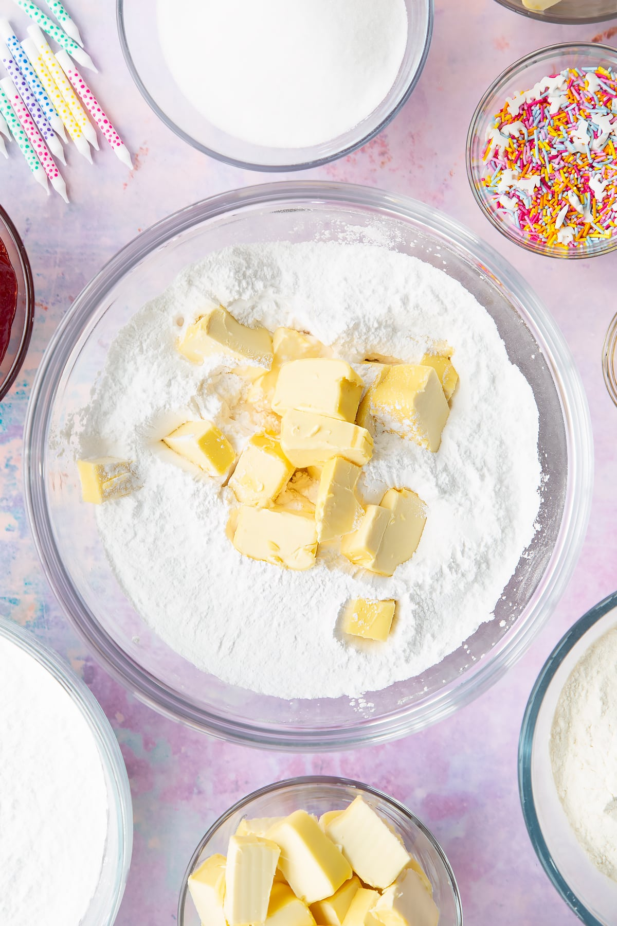 Vegan butter, icing sugar, vanilla extract and plant milk in a glass mixing bowl. Ingredients to make vegan birthday cake surround the bowl.