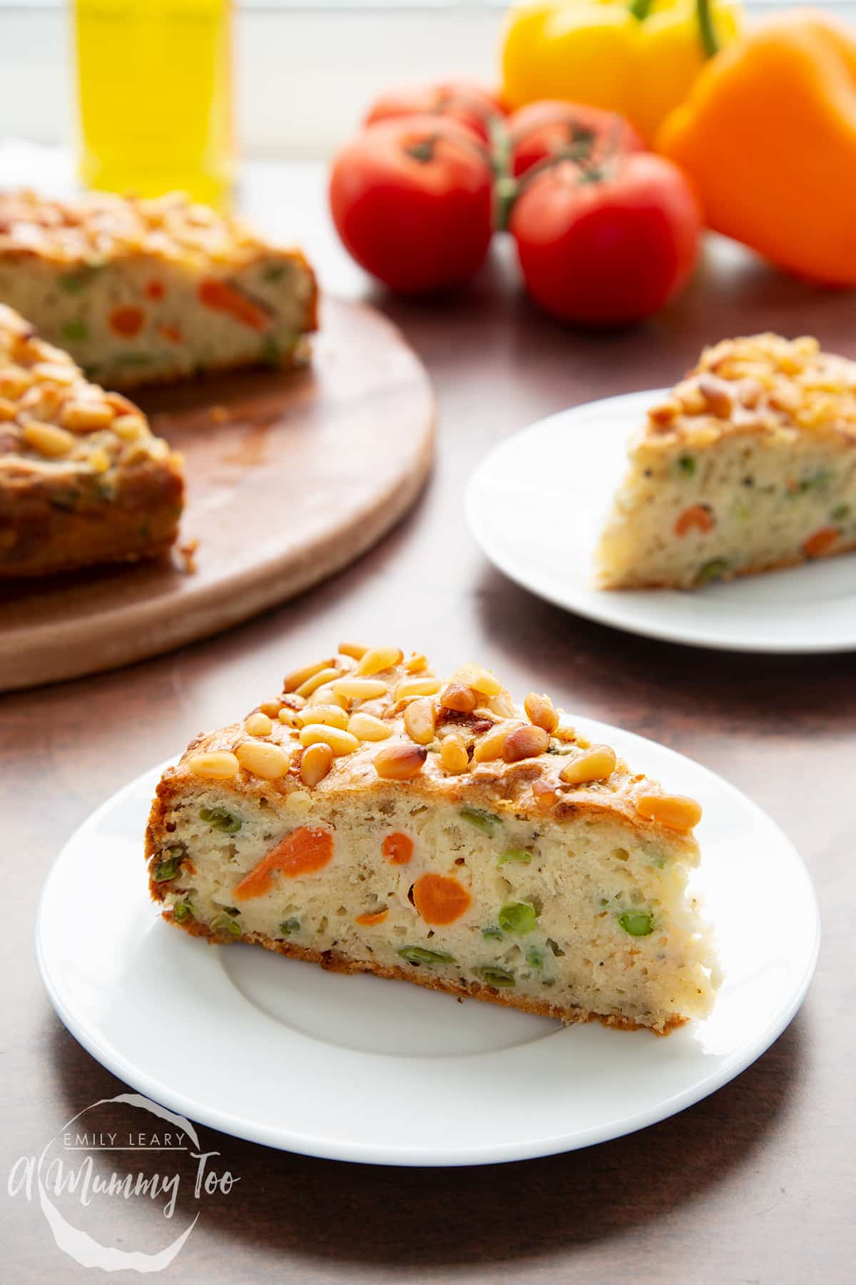 A slice of vegetable cake on a white plate with more cake in the background.