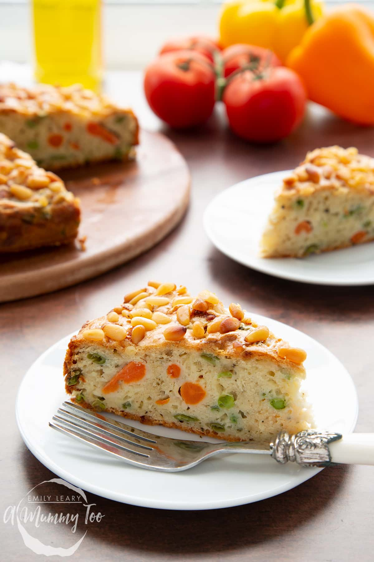 A slice of vegetable cake on a white plate with a fork. There is more cake in the background.