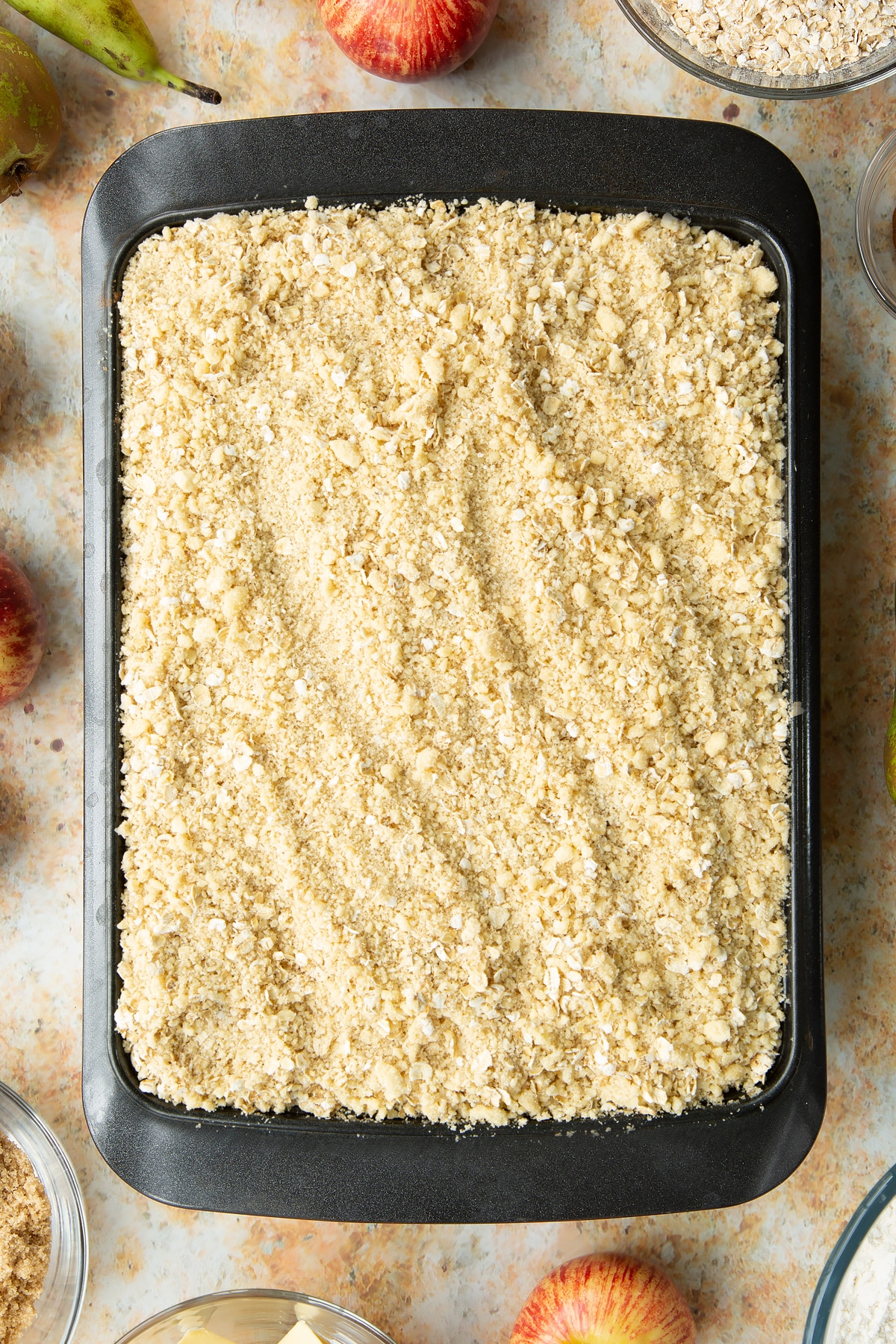 Oat crumble on top of apples and pears in a metal tray.