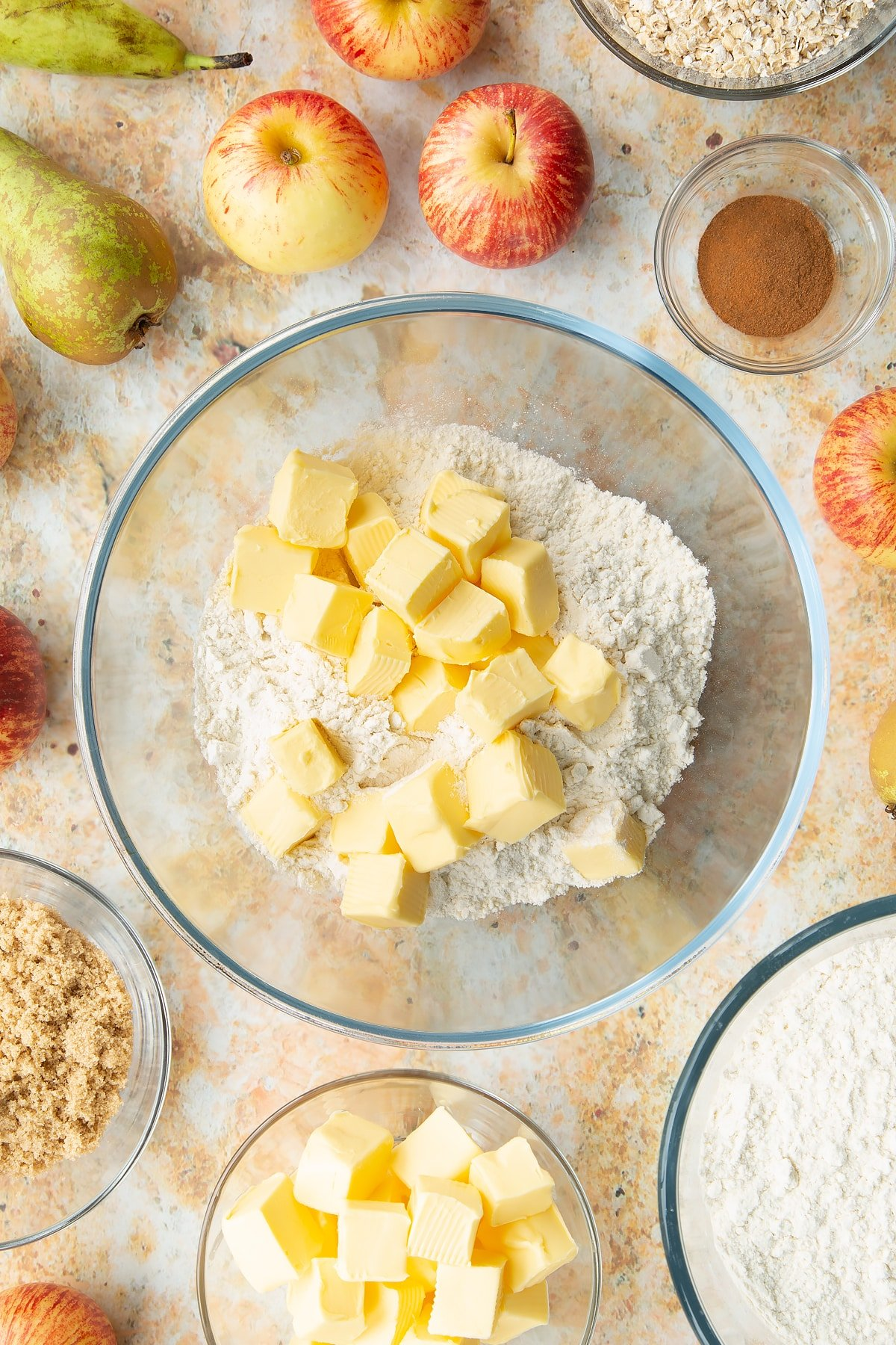 Flour and cold cubed butter in a mixing bowl. Ingredients to make easy apple pear crumble surround the bowl.