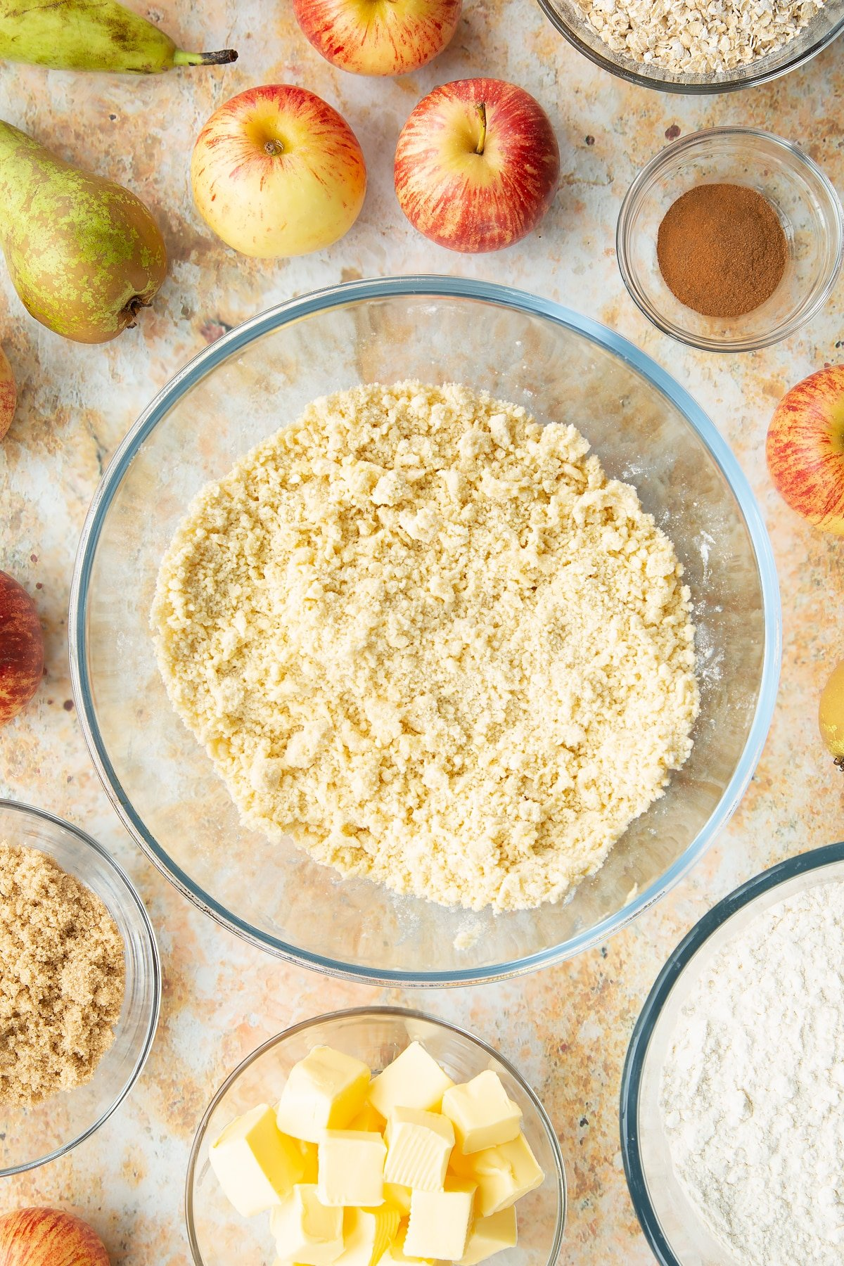 Flour and butter rubbed together in a mixing bowl. Ingredients to make easy apple pear crumble surround the bowl.