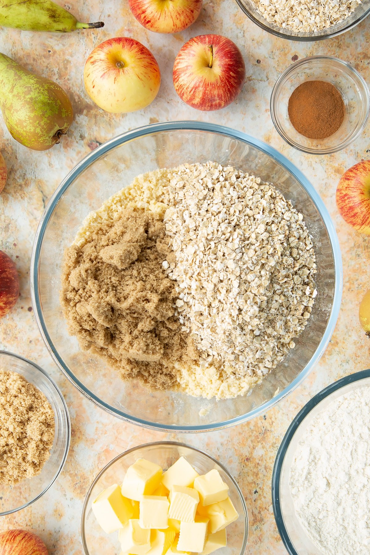 Flour and butter rubbed together in a mixing bowl with sugar and oats on top. Ingredients to make easy apple pear crumble surround the bowl.
