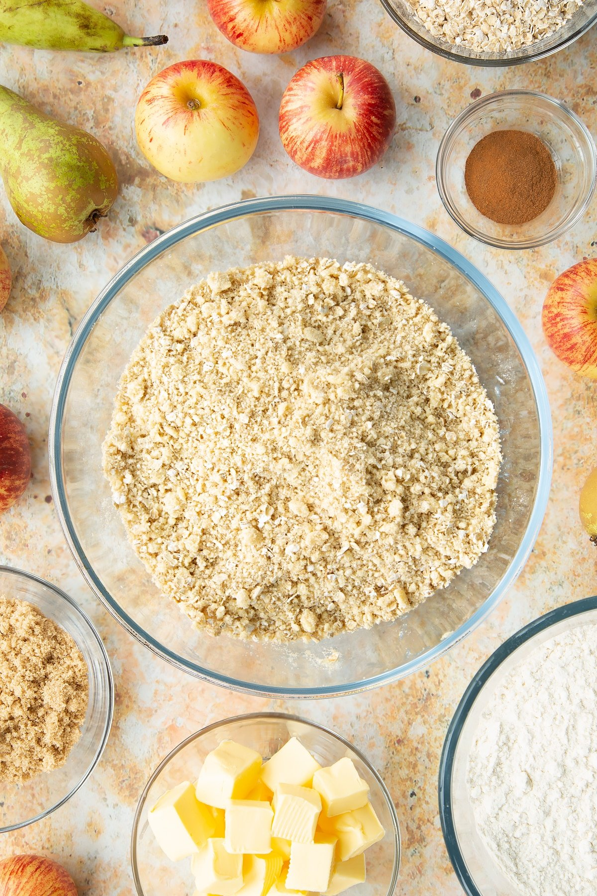 Flour, butter oats and sugar mixed together in a mixing bowl. Ingredients to make easy apple pear crumble surround the bowl.