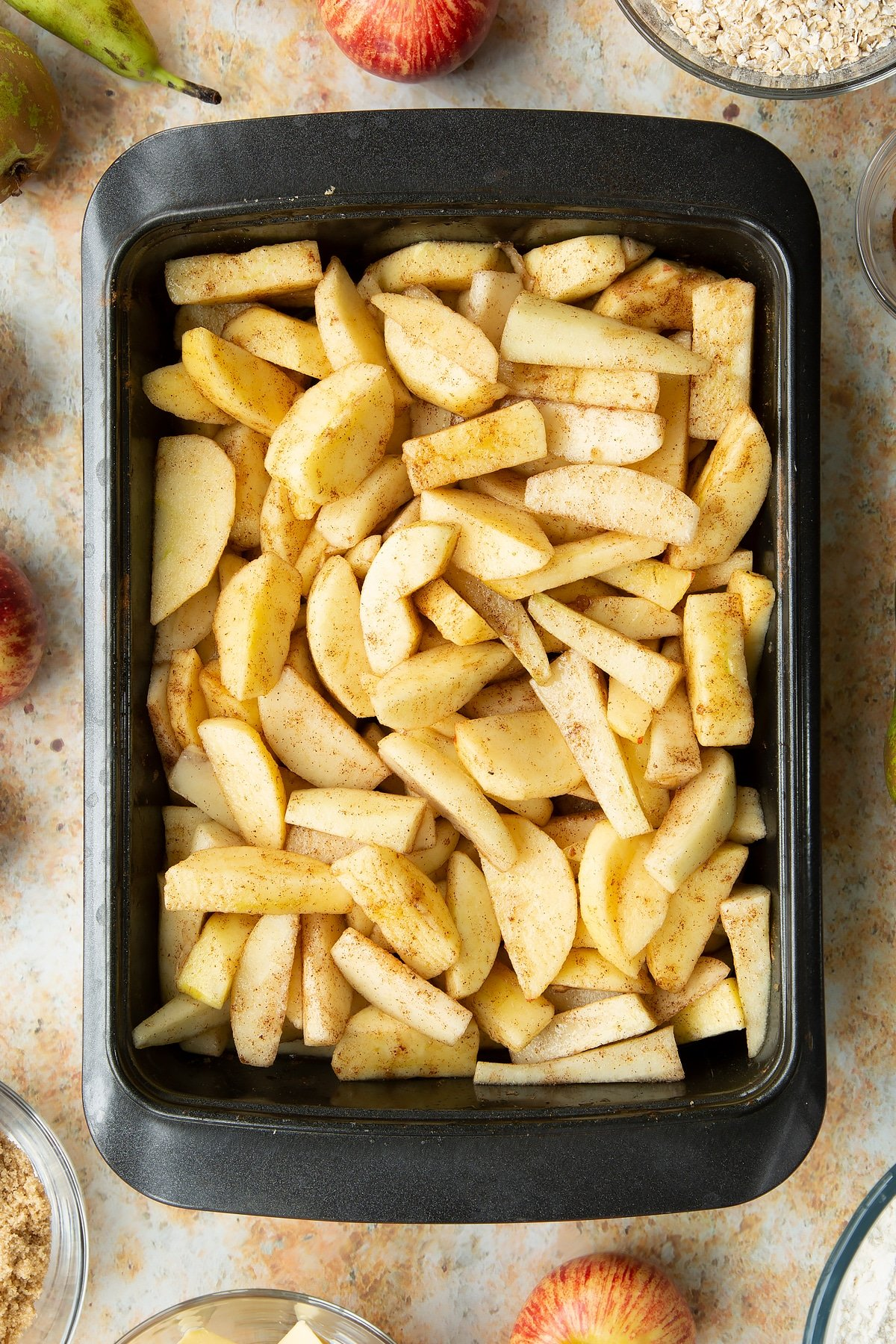 Peeled apple and pear wedges mixed with light brown sugar and cinnamon in a greased tray.