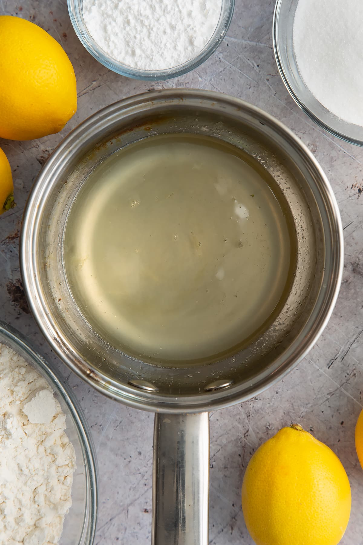 Hot lemon drizzle syrup in a small metal pan. Ingredients to make lemon drizzle cake surround the pan.
