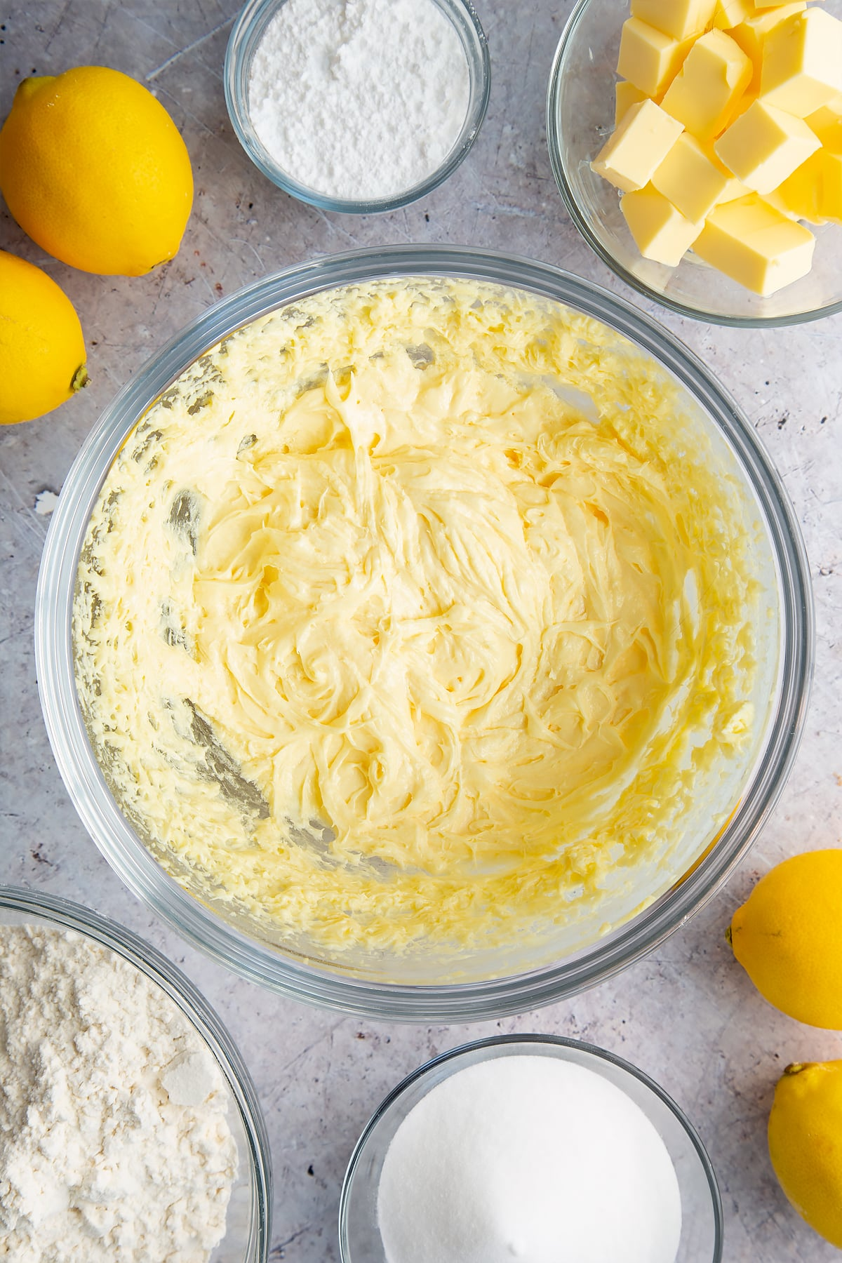Butter, sugar and eggs creamed together in a glass bowl. Ingredients to make lemon drizzle cake surround the bowl.