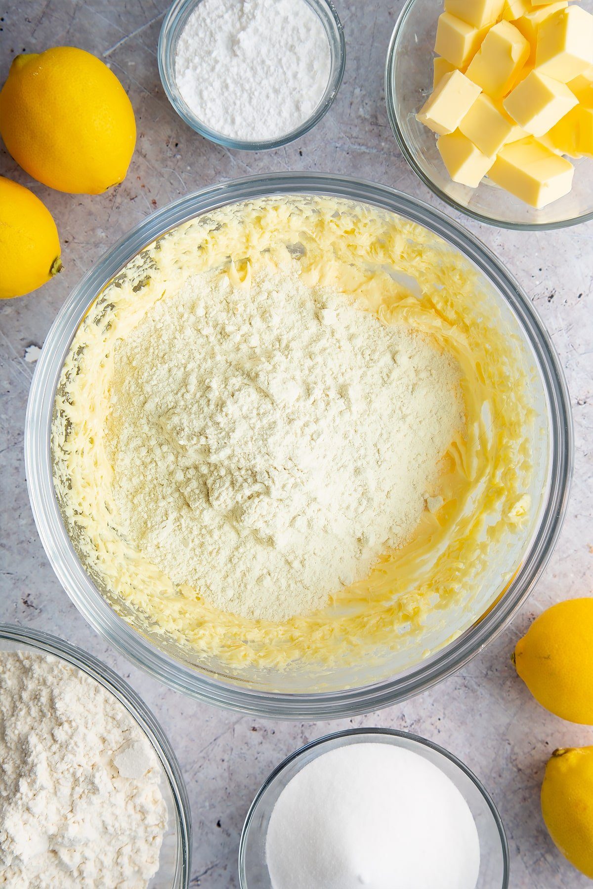 Butter, sugar and eggs creamed together with flour on top in a glass bowl. Ingredients to make lemon drizzle cake surround the bowl.
