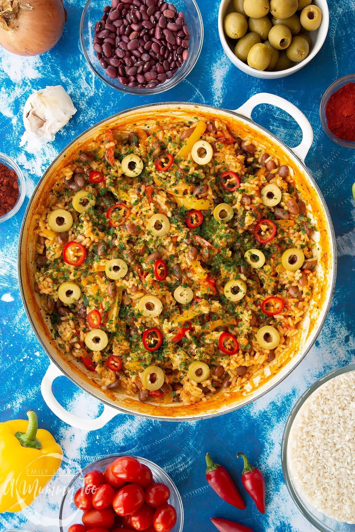 Easy Spanish rice and beans in a large shallow pot, garnished with olives, chilli and parsley.