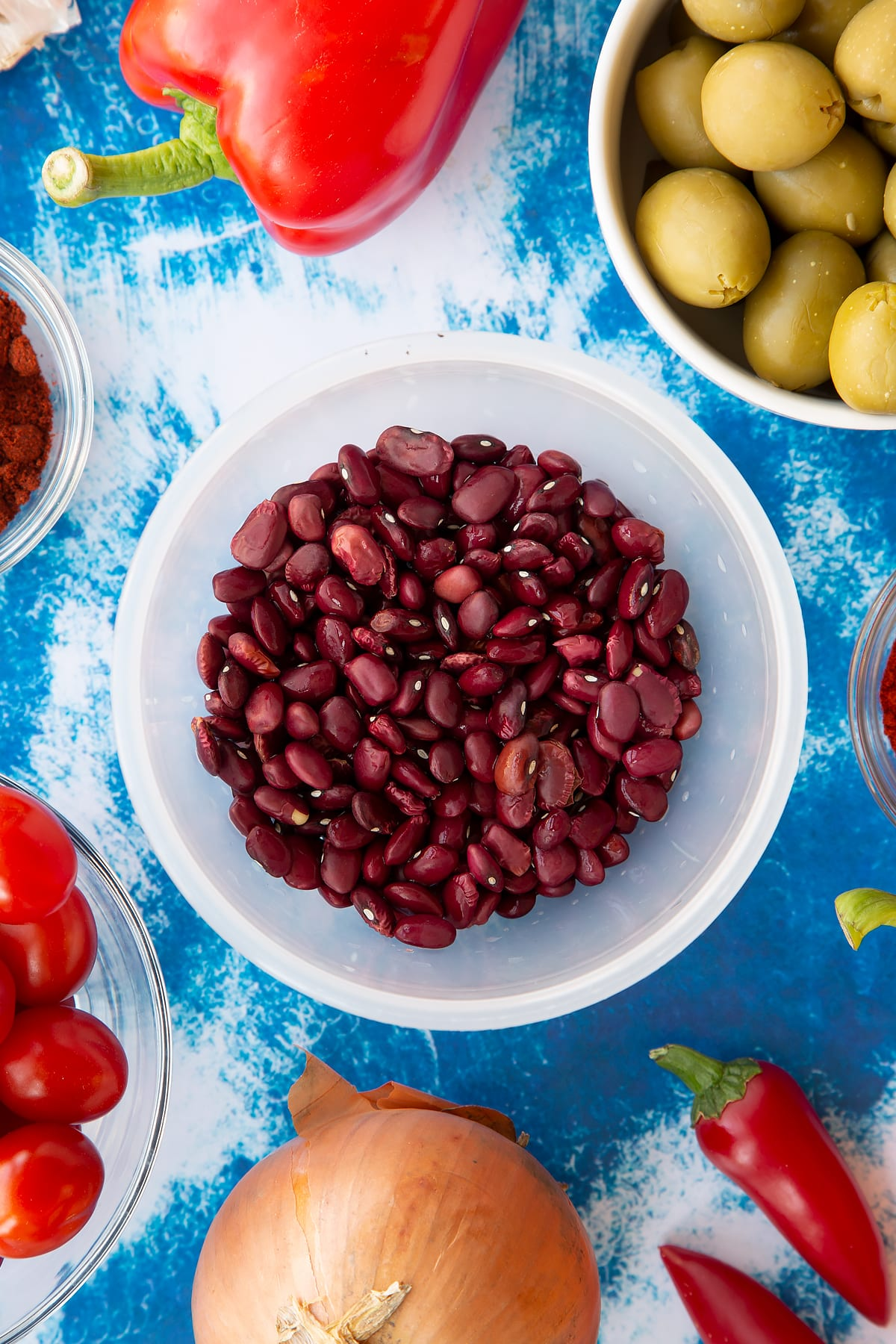 Dried kidney beans in a small pot. Ingredients to make easy Spanish rice and beans surround the pot.