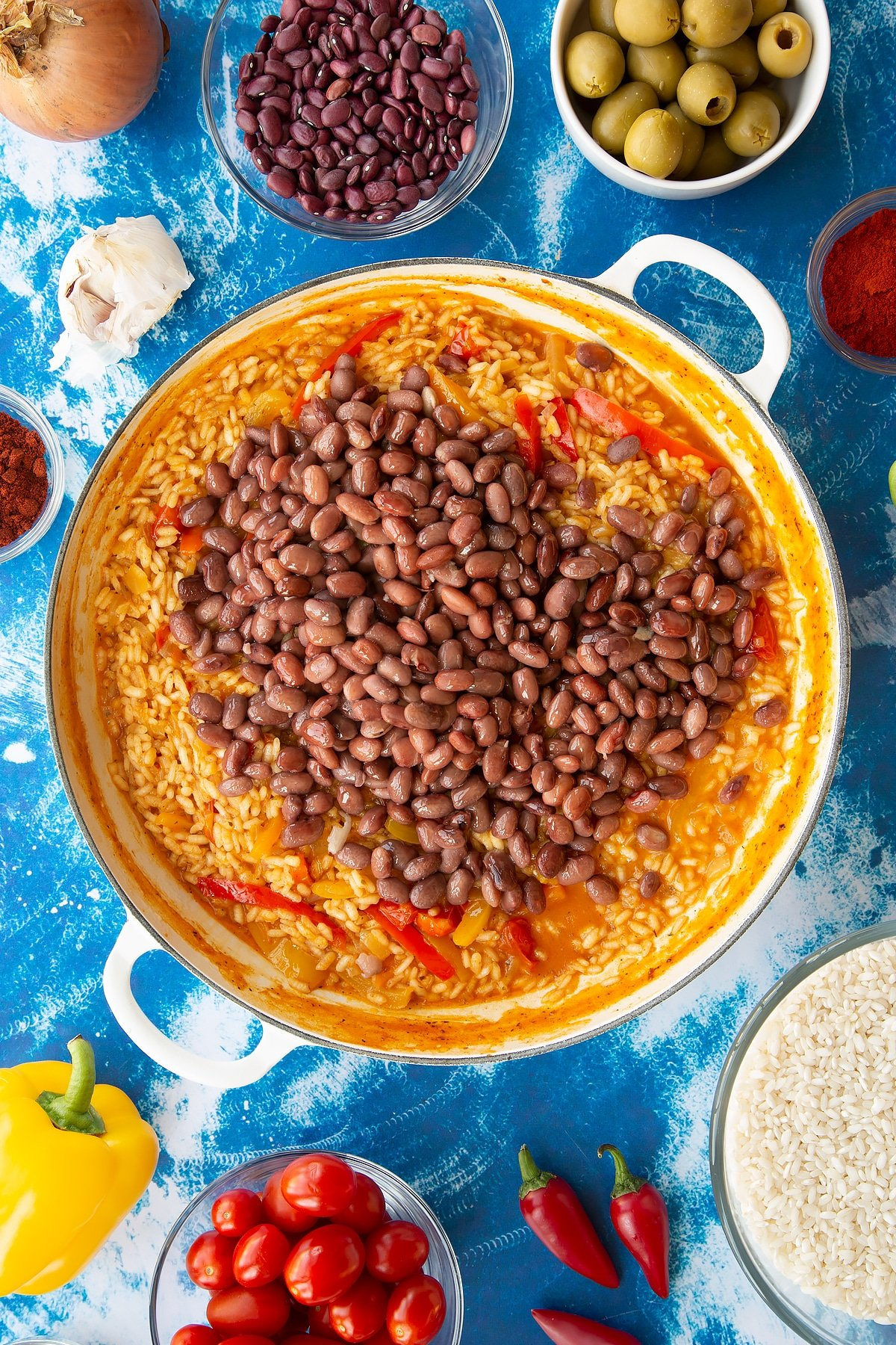 Spanish rice in a large shallow pot with kidney beans on top.